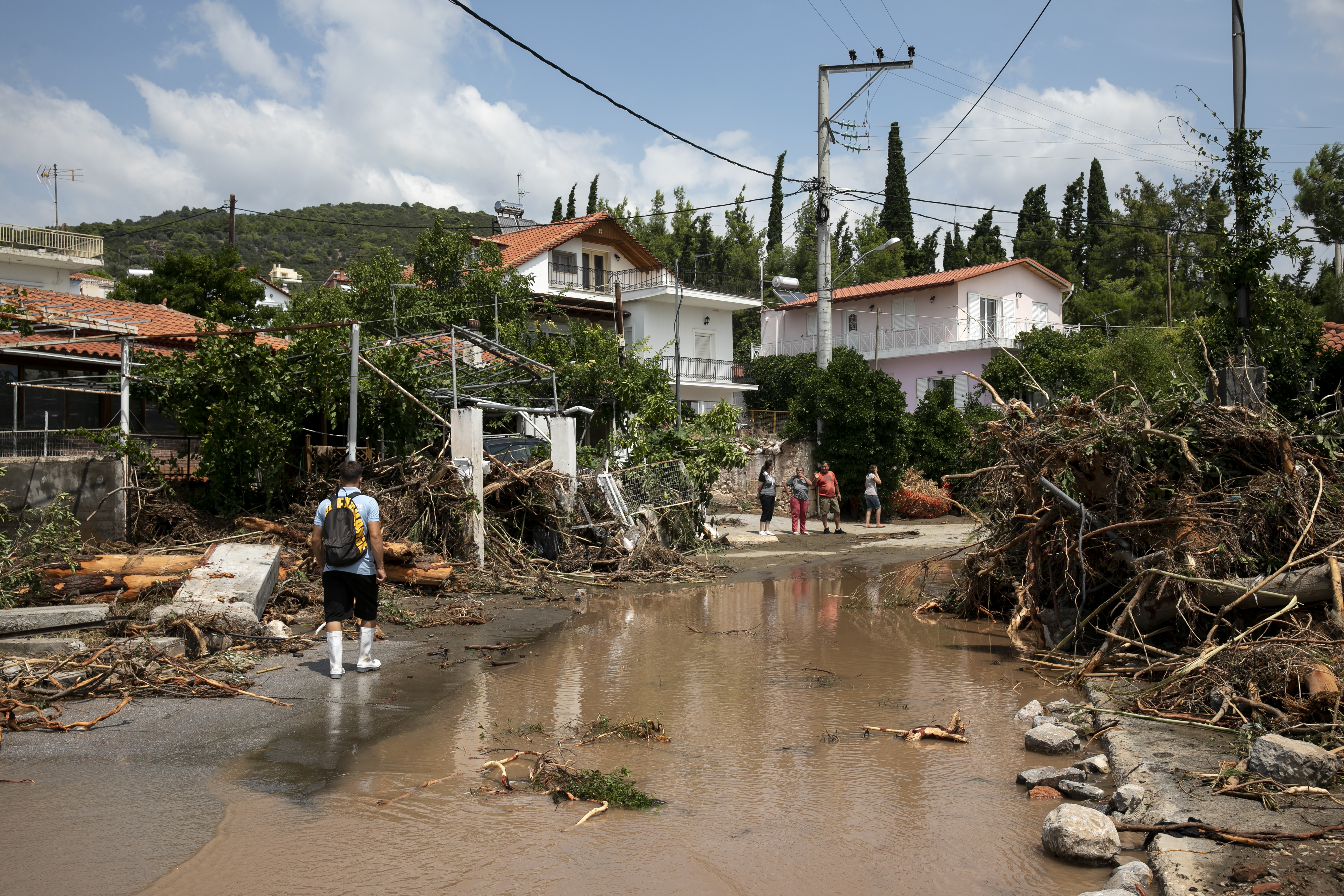 A man walks at a street full of debris following a storm at the village of Politika, on Evia island, northeast of Athens, on Aug. 9, 2020.