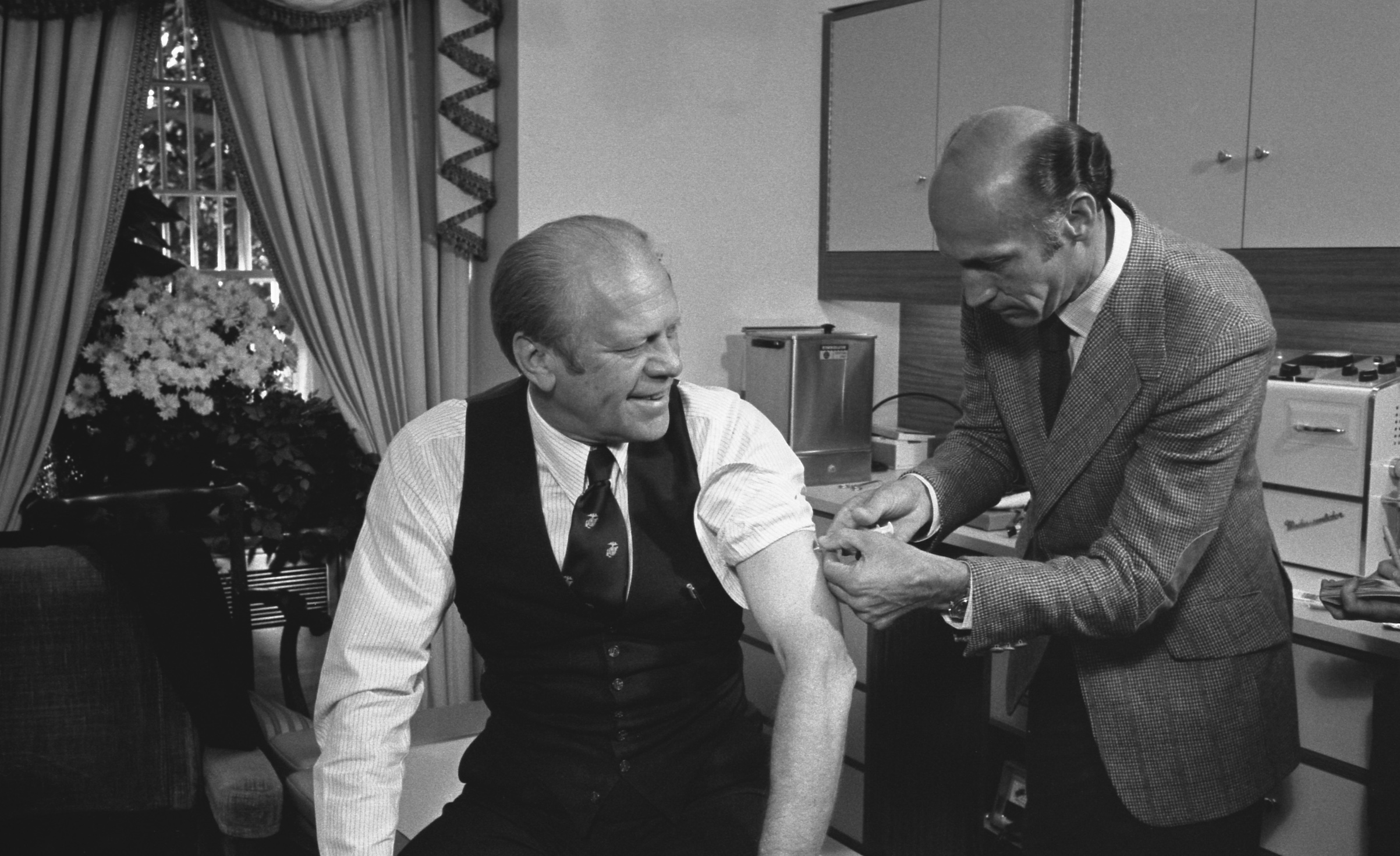 President Gerald Ford is injected with a swine flu inoculation by White House physician Dr. William Lukash, in Washington, D.C., Oct. 14, 1976.
