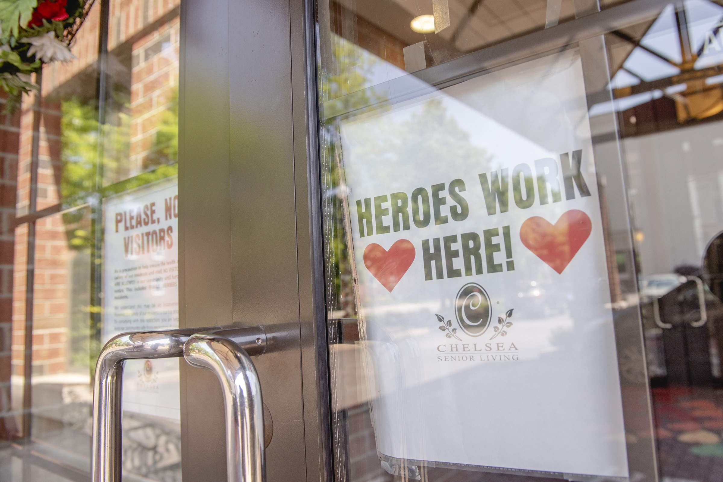 A sign reading  Heroes Work Here  is displayed in a window of the Maple Pointe Assisted Living facility in Rockville Centre, New York, on June 9
