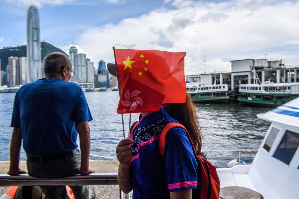 A woman holds Chinese and Hong Kong flags as she disembarks from a boat in Victoria Harbour on the 23rd anniversary of the city's handover from Britain in Hong Kong on July 1, 2020.