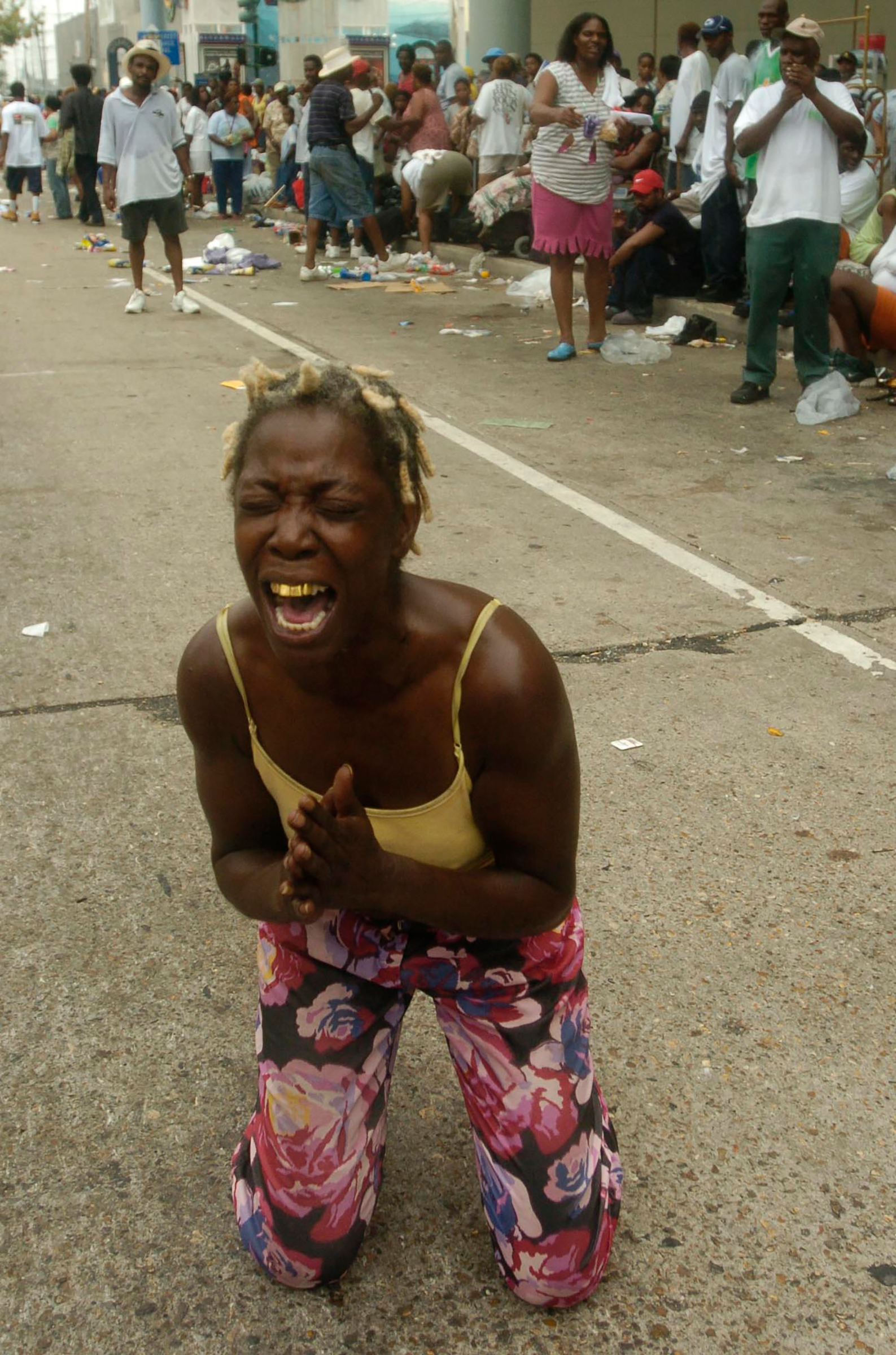 Angela Perkins drops to her knees asking for help among thousands of people gathered at the New Orleans Convention Center waiting in the aftermath of Hurricane Katrina on Sept. 1, 2005