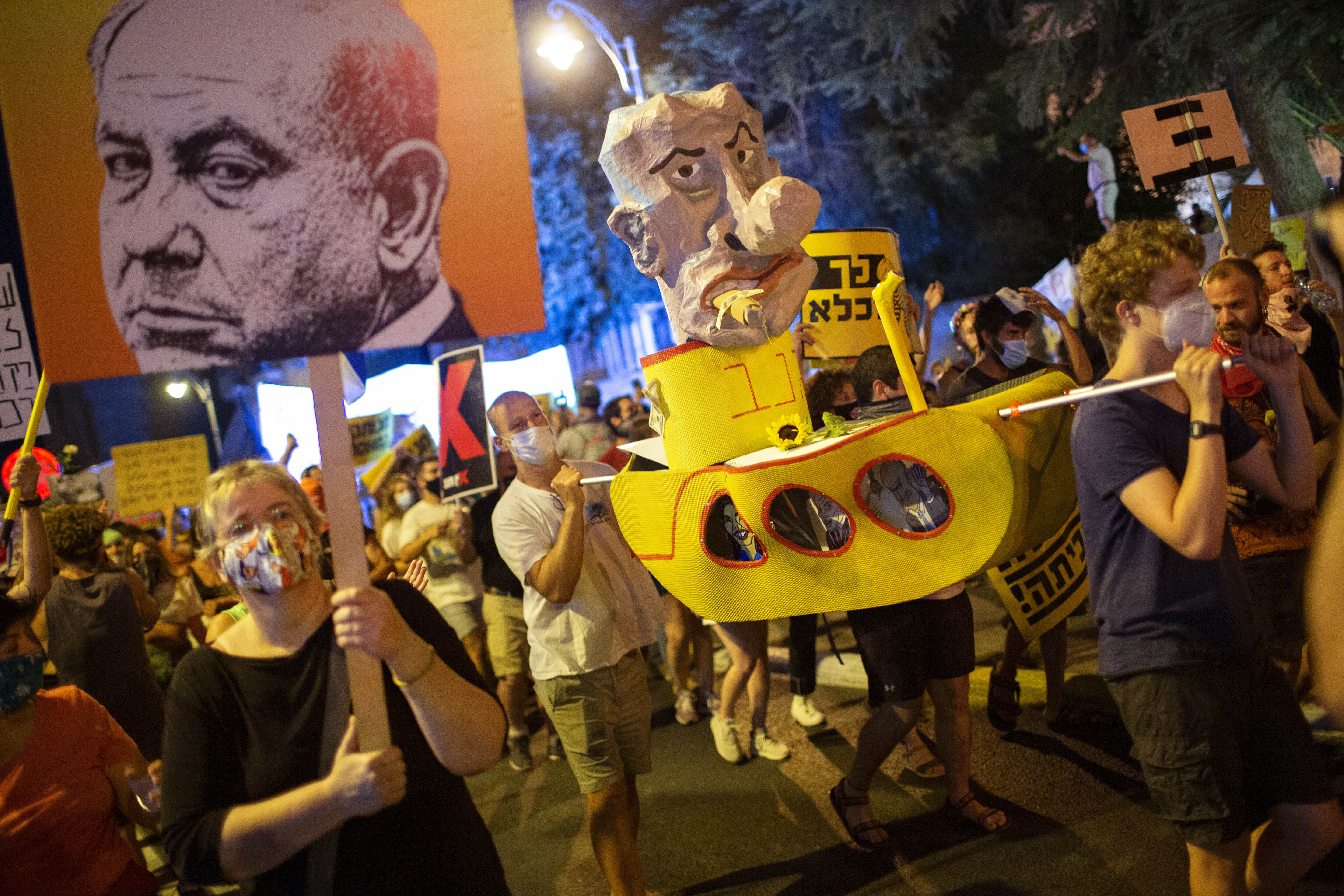 Demonstrators chant slogans and hold signs during a rally against Israel's Prime Minister Benjamin Netanyahu outside his residence in Jerusalem, Aug 1, 2020.