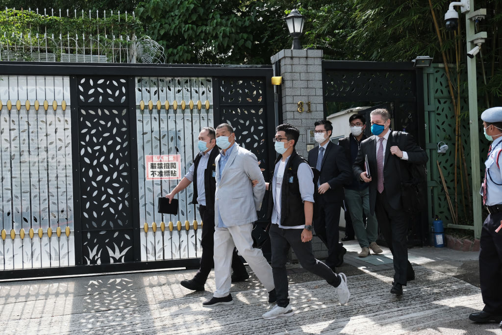 Jimmy Lai, chairman of Next Media Ltd., second left, is led away from his residence by law enforcement officials in Hong Kong, China, on Monday, Aug. 10, 2020. Hong Kong police arrested media tycoon and prominent democracy activist Jimmy Lai under a national security law passed in late June for allegedly colluding with foreign forces.