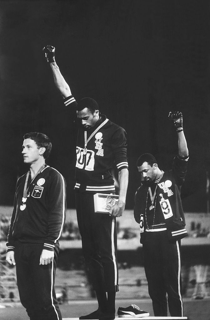 American track and field athletes Tommie Smith (center) and John Carlos (right), first and third place winners in the 200 meter race, protest with the Black Power salute as they stand on the winner's podium at the Summer Olympic games, Mexico City, Mexico, Oct. 19, 1968.