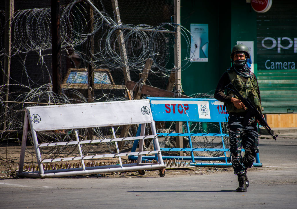 An Indian paramilitary trooper stands guard in front of his bunker in the city of Srinagar in Indian administered-Kashmir on August 5, 2020.