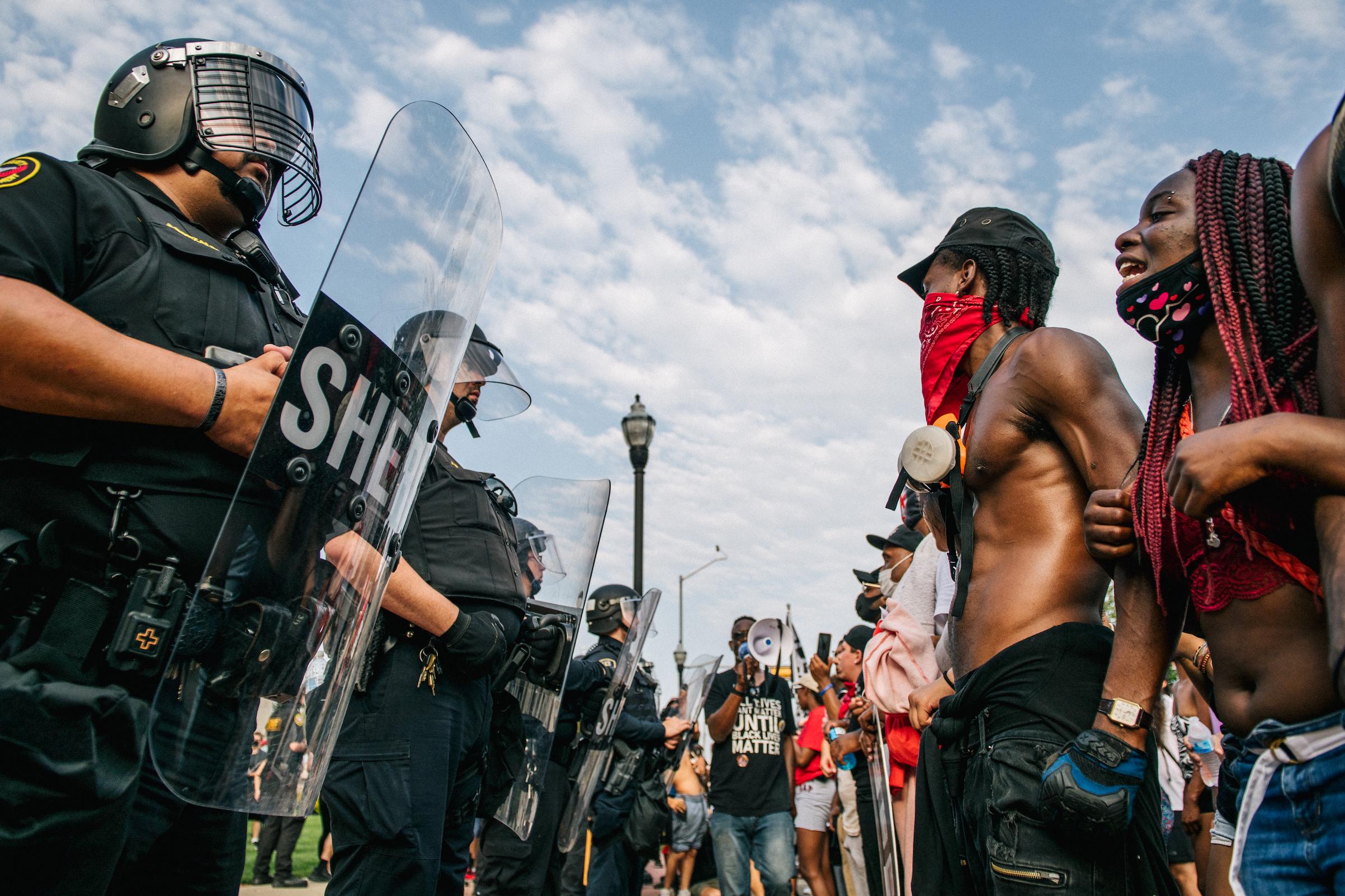 Demonstrators form a line in front of law enforcement on Aug. 24, 2020, in Kenosha, Wisc.