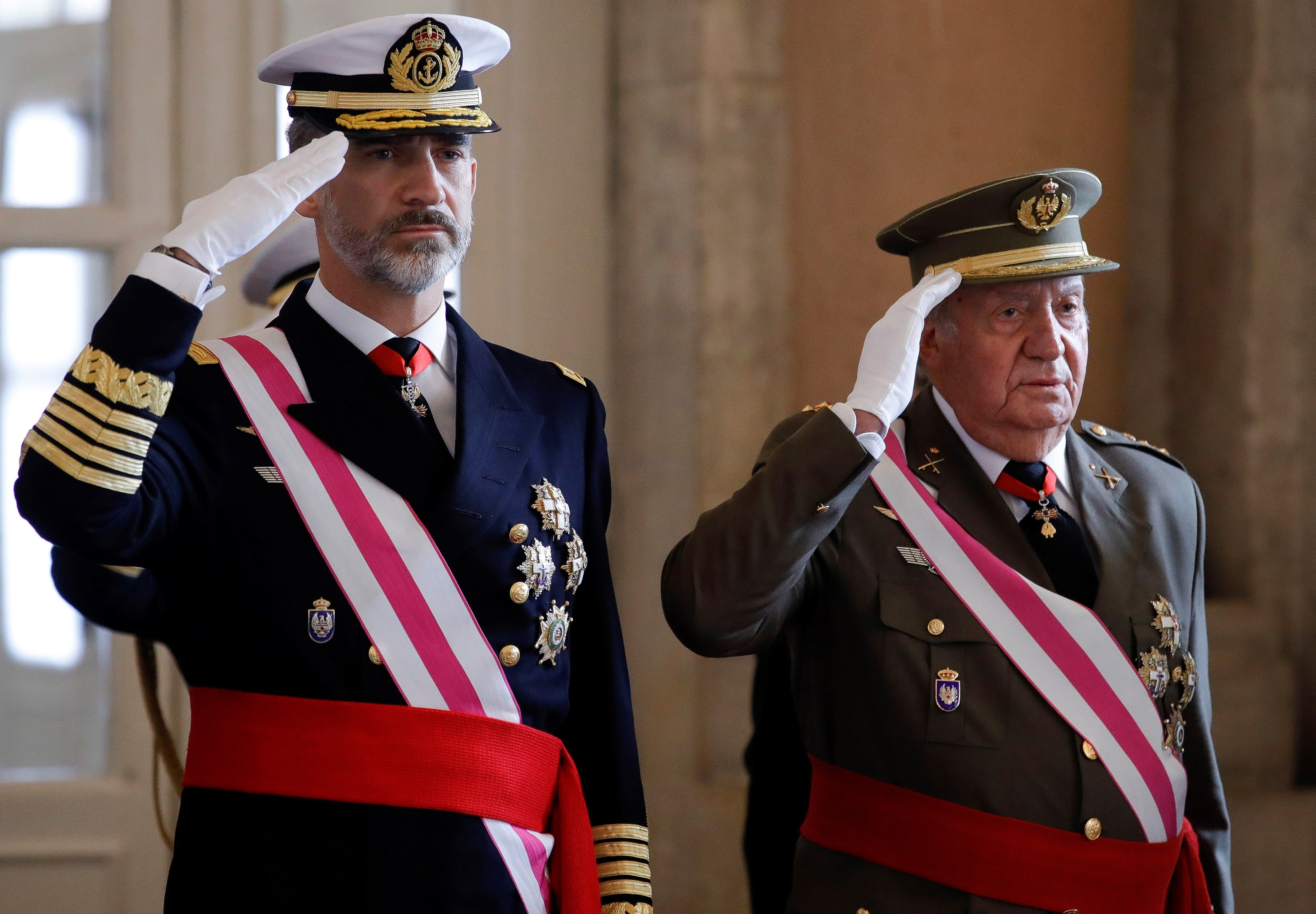 Spain's King Felipe VI and his father Juan Carlos I salute during Epiphany Day celebrations at the Royal Palace in Madrid on Jan. 6, 2018.