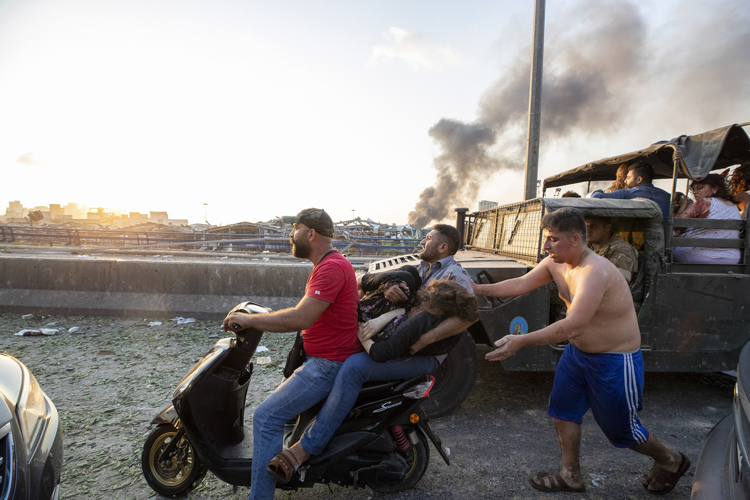 Wounded people evacuate after a massive explosion in Beirut.
