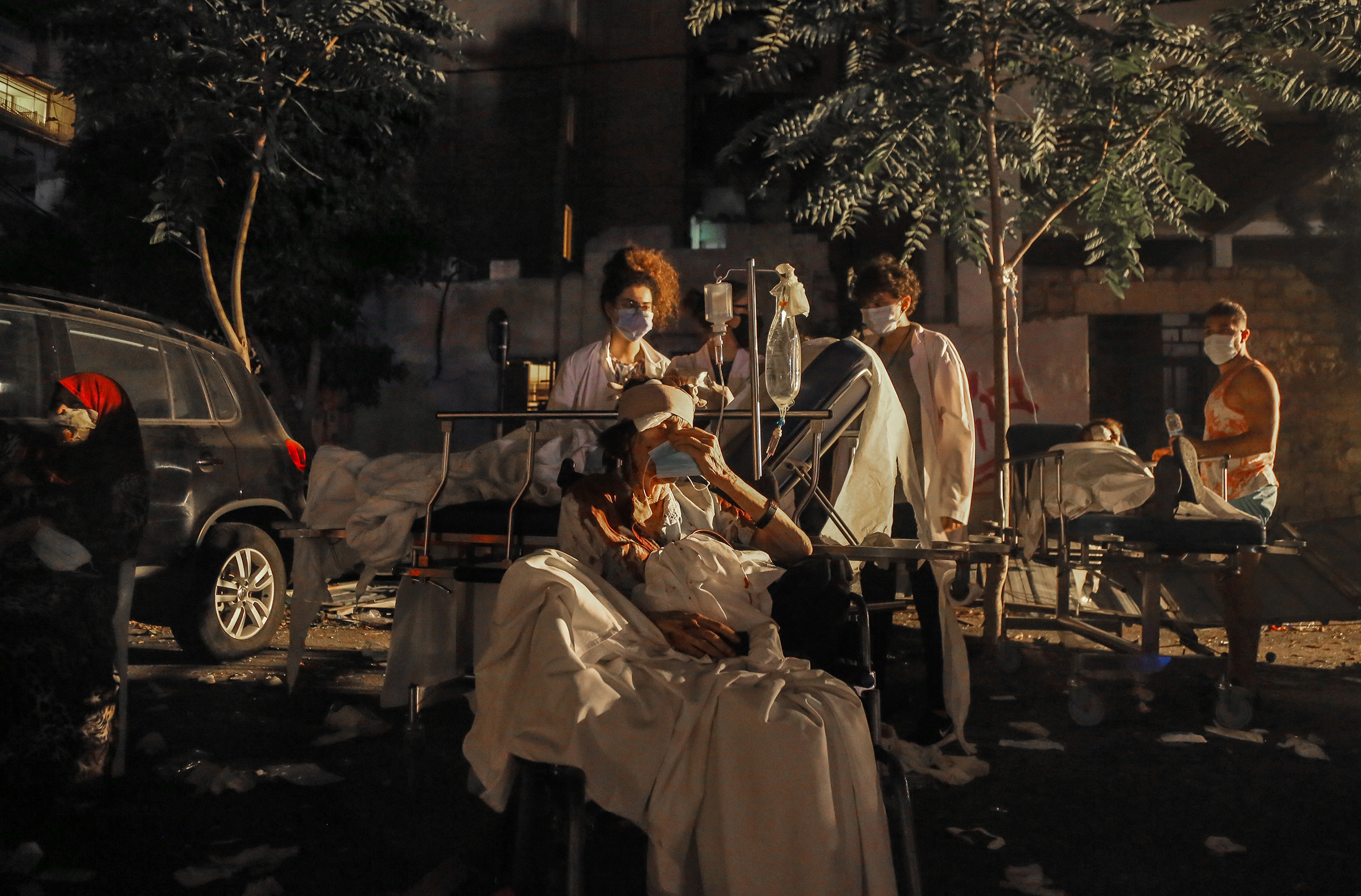 Wounded people receive treatment in the parking lot of Al Roum Hospital, following a a massive explosion in Beirut's port on August 4, 2020.
