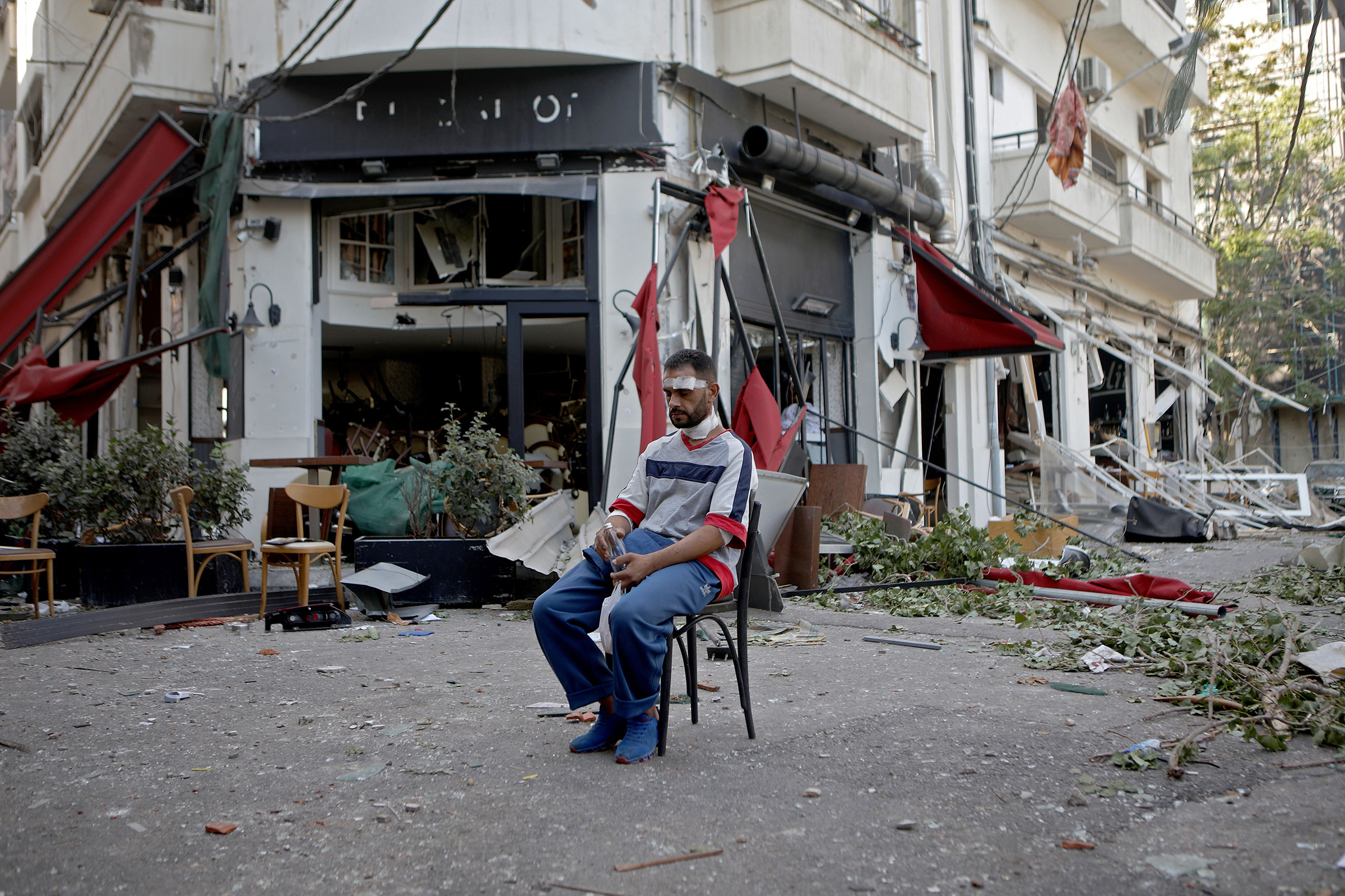 An injured man sits next to a restaurant in the Mar Mikhael neighborhood of Beirut on August 5 in the aftermath of the massive explosion.