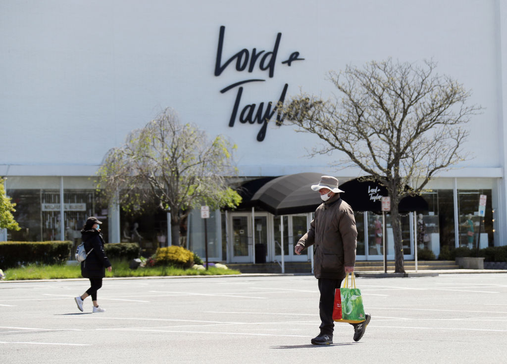 Pedestrians walk past a shuttered Lord and Taylor department store following their filing for bankruptcy amid the COVID-19 pandemic on May 12, 2020 in Garden City, New York.