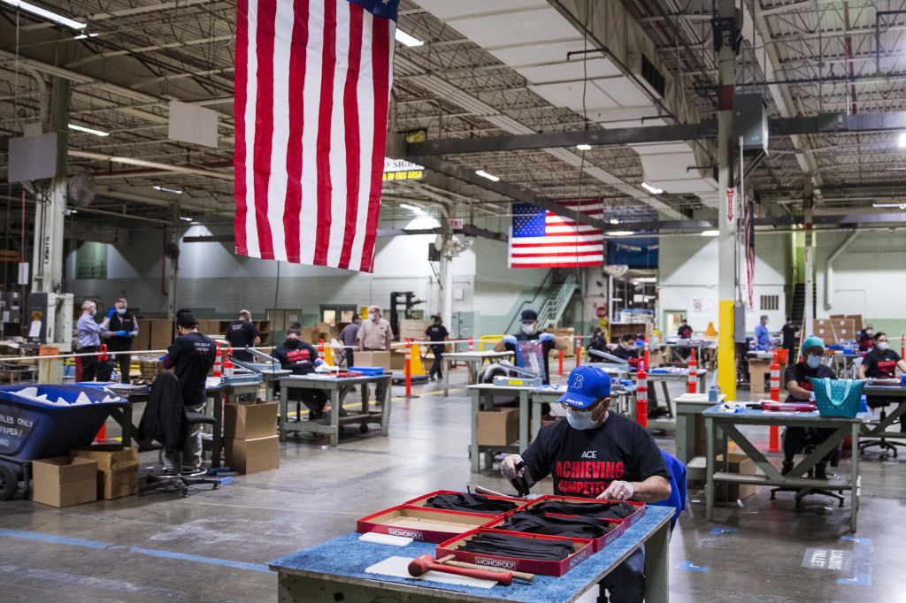 Workers wearing protective masks and gloves assembles face shields at the Cartamundi-owned Hasbro manufacturing facility in East Longmeadow, Massachusetts, U.S., on Wednesday, April 29, 2020.