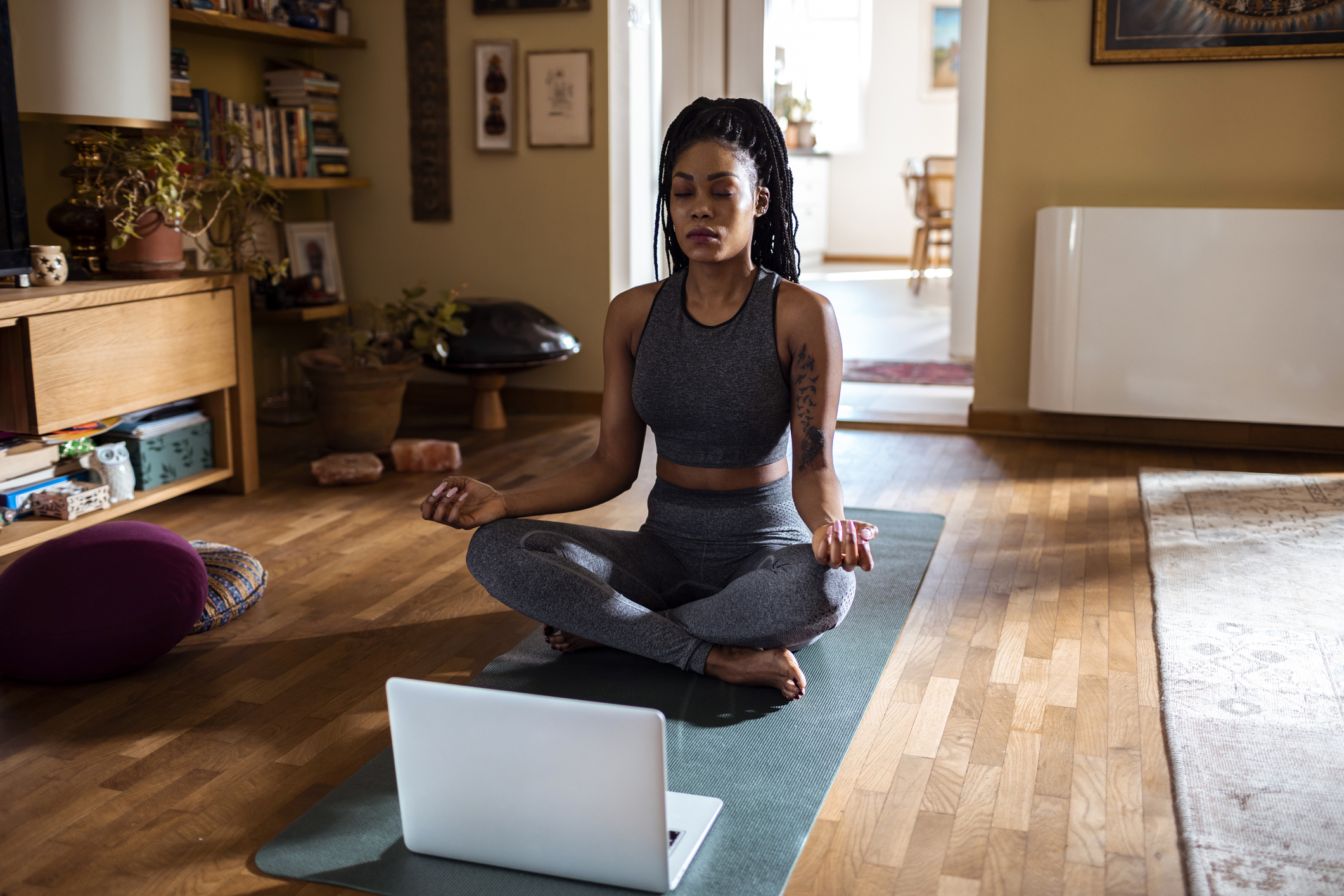 Close up of a young woman meditating at home.