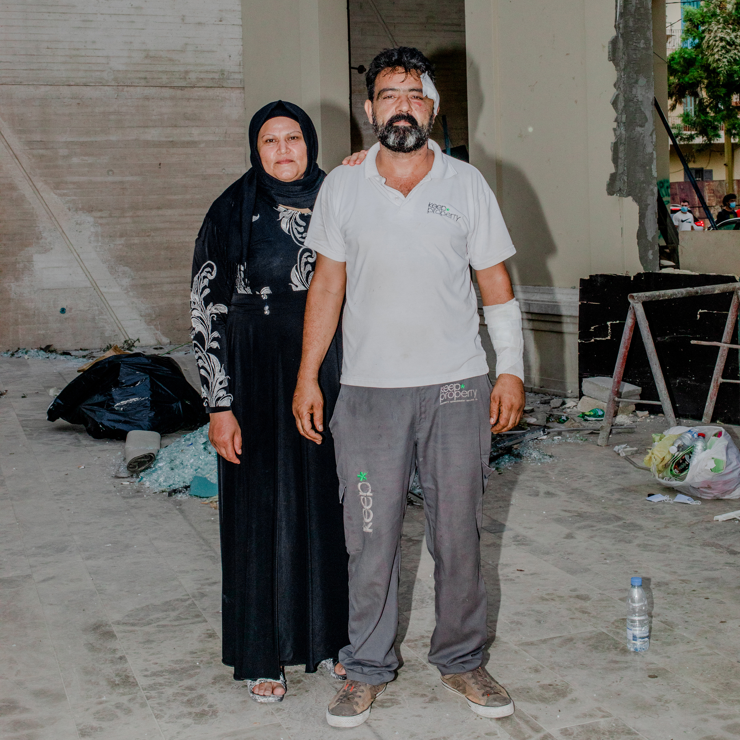 "Riad Hussein Al Hussein and his wife Fatima Al Abid in the Mar Mikhael neighborhood of Beirut on Aug. 7. He was buying vegetables there three days earlier when he heard a small explosion. He asked the seller whether he thought it was a shell or a bomb, and where it had landed.  Our discussion lasted approximately one minute and was interrupted by another sound of explosion, one way louder,"" he recalls. ""I shouted and said we needed to hurry inside the shop, and that is when I was hit by the glass.  He later went back to the building where he was injured to assist with cleaning up.  I wanted to help like I had been helped,  he said.  I wanted to pay it forward."