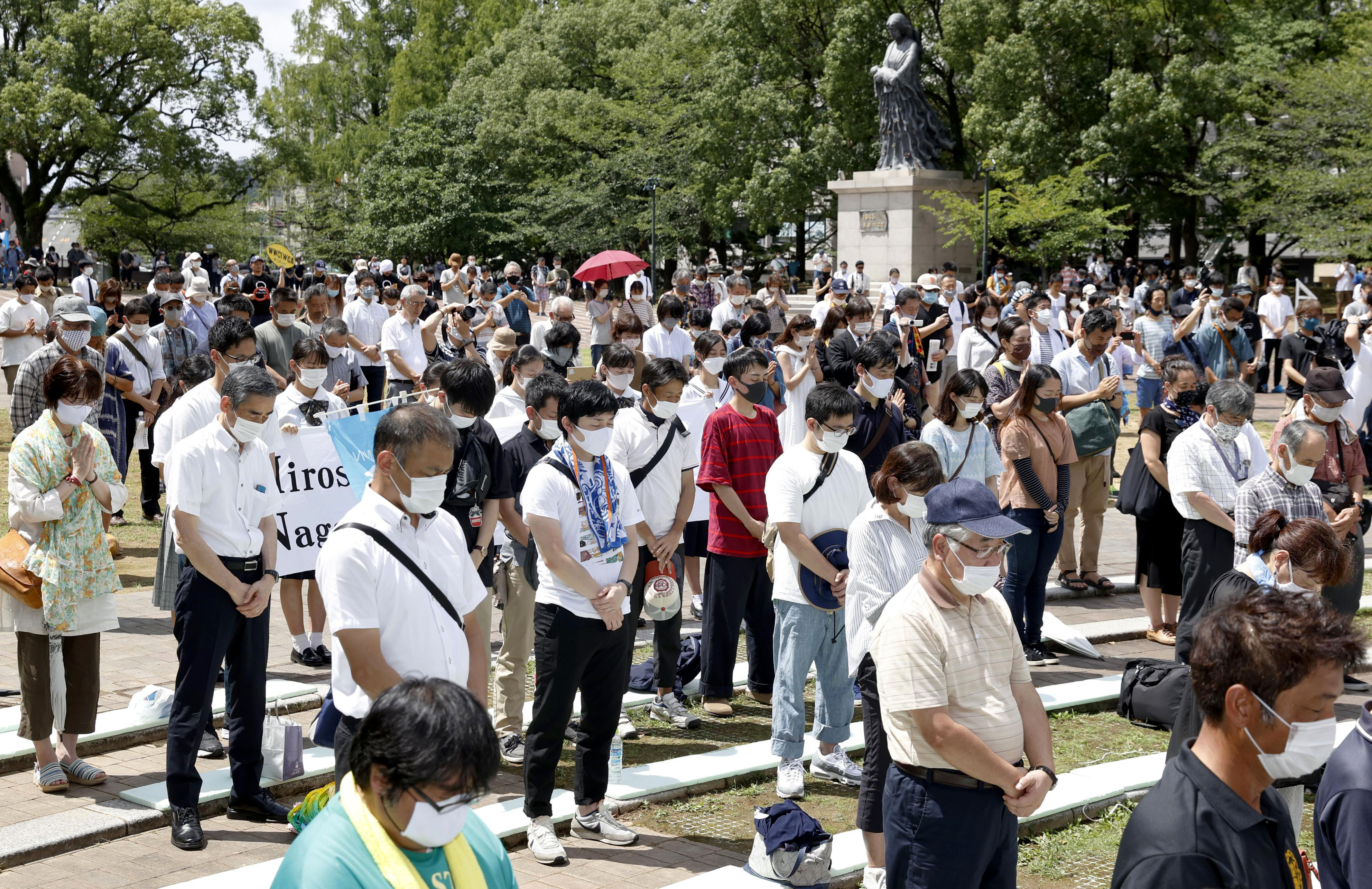 People offer silent prayer for the victims of U.S. atomic bombing at the time when the bomb was dropped, at the Atomic Bomb Hypocenter Park in Nagasaki, southern Japan, Aug. 9, 2020.