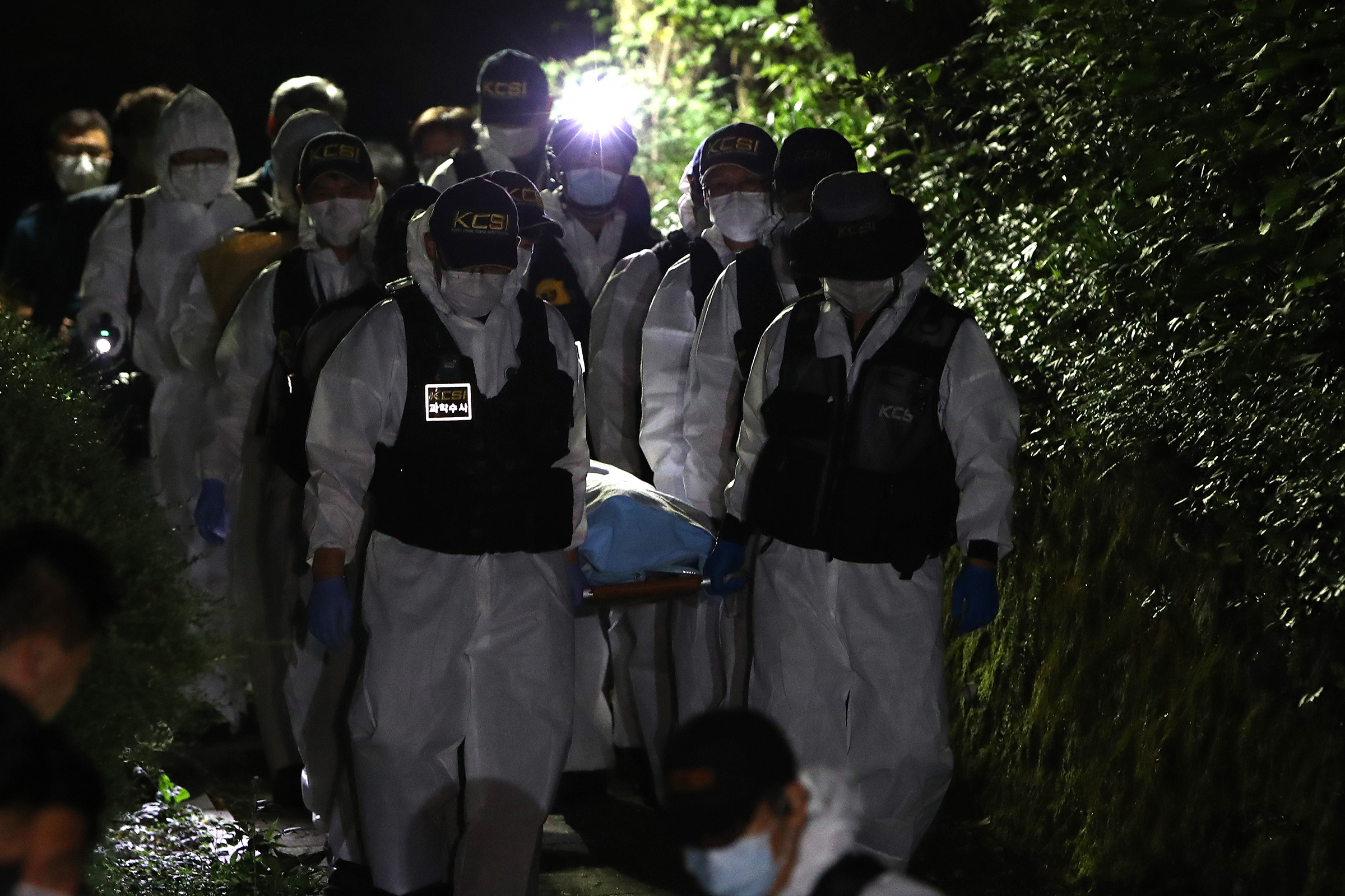 Police officers carry Park's body on July 10