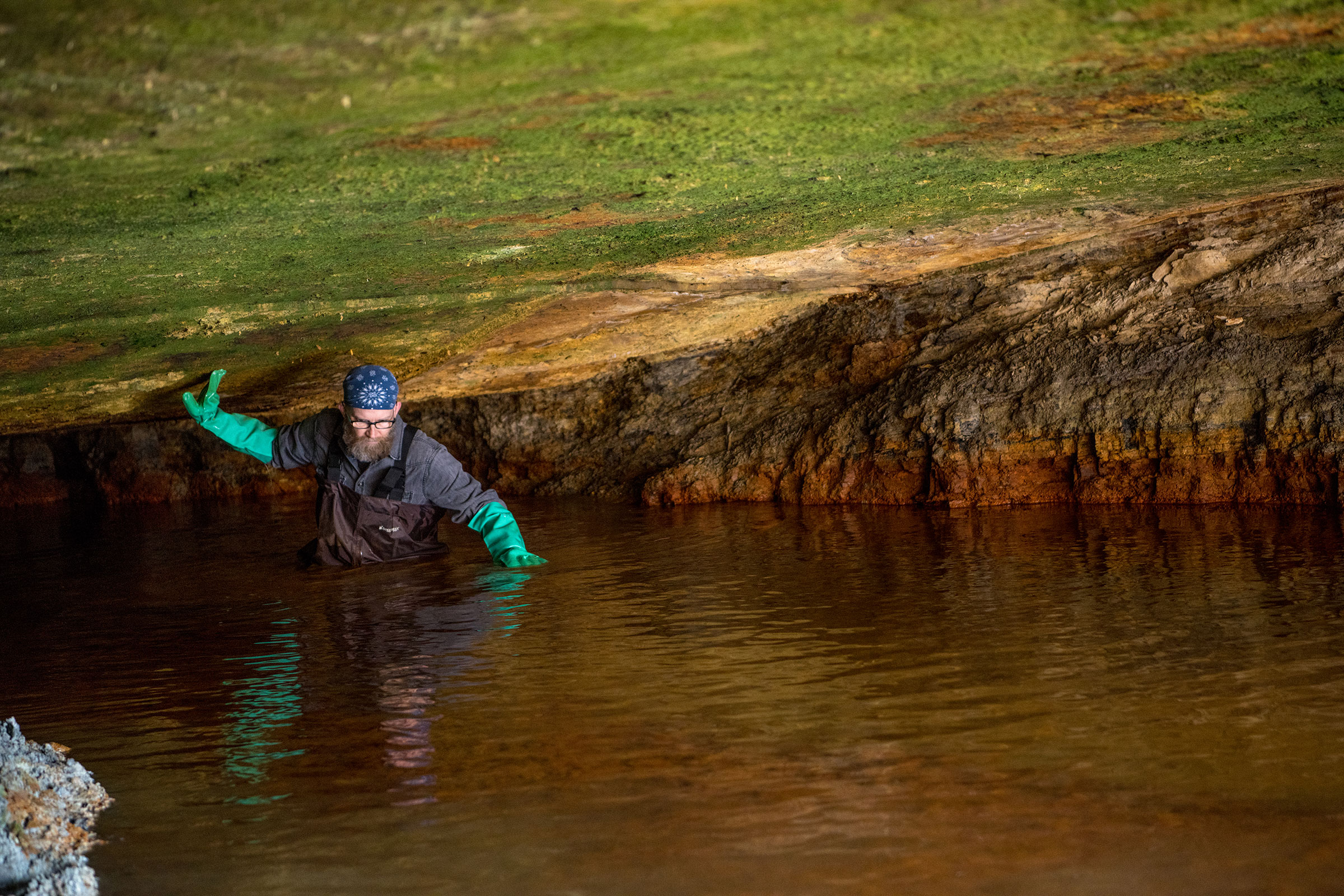 John Sabraw deep in acid mine drainage in Bat Gate cave, Sulfur Springs Hollow, Ohio.