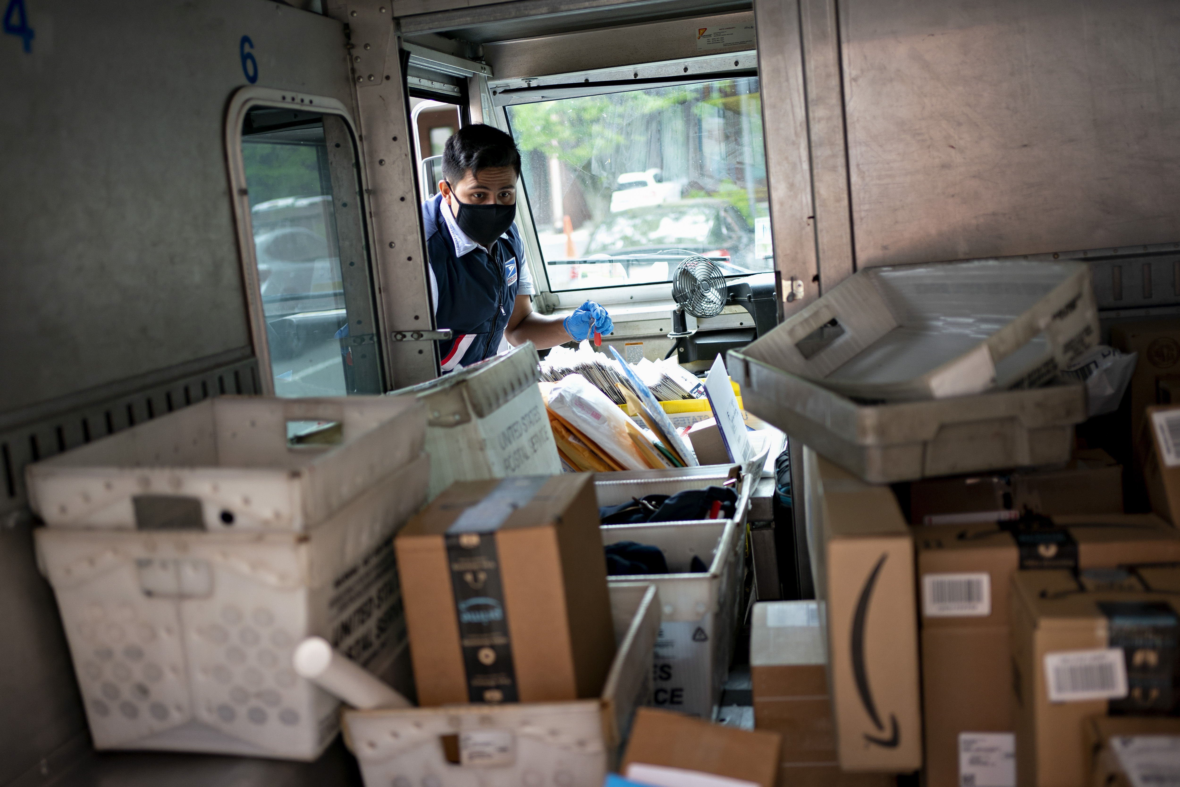 A United States Postal Service (USPS) letter carrier wears a protective mask and gloves while preparing to sort parcels in Fairfax, Virginia on May 19, 2020.