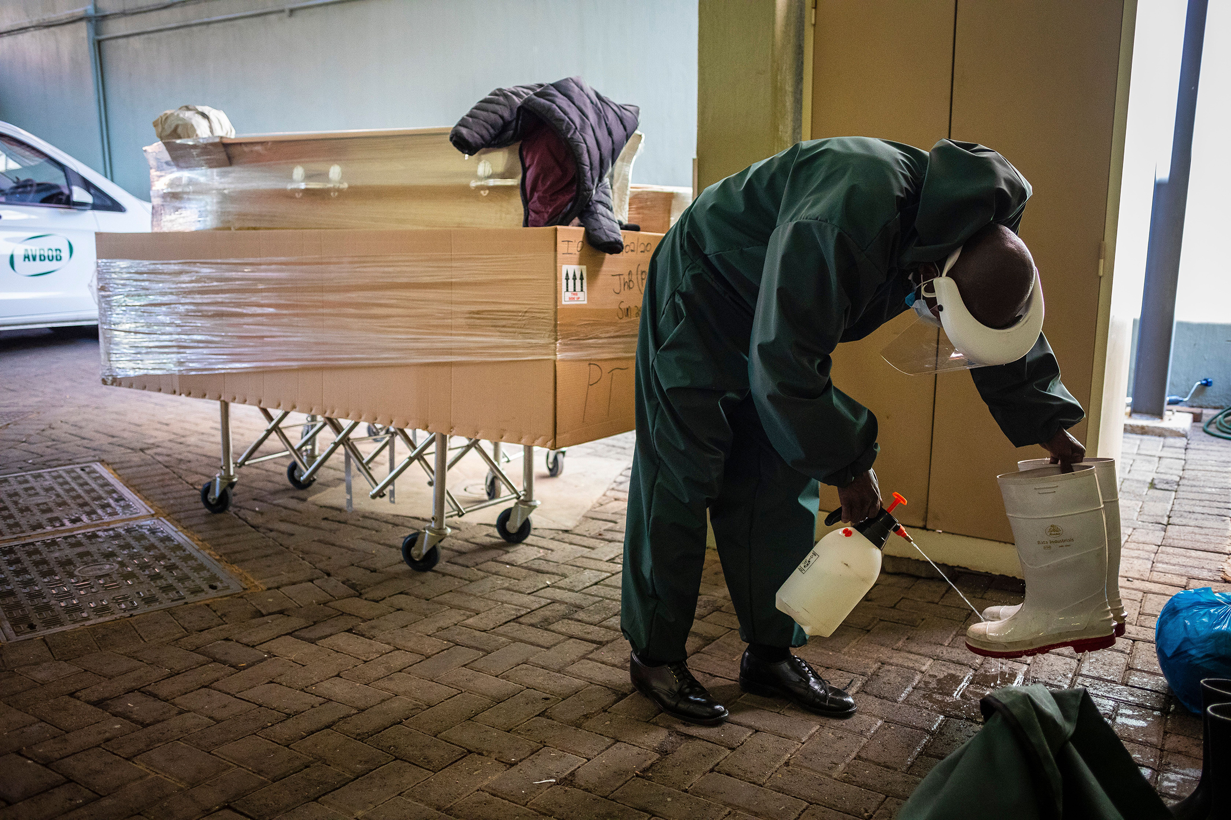 Undertaker Steven Ntuli sterilizes his boots after collecting a suspected Covid-19 victim from a government hospital in Johannesburg, South Africa, on 21 July 2020.