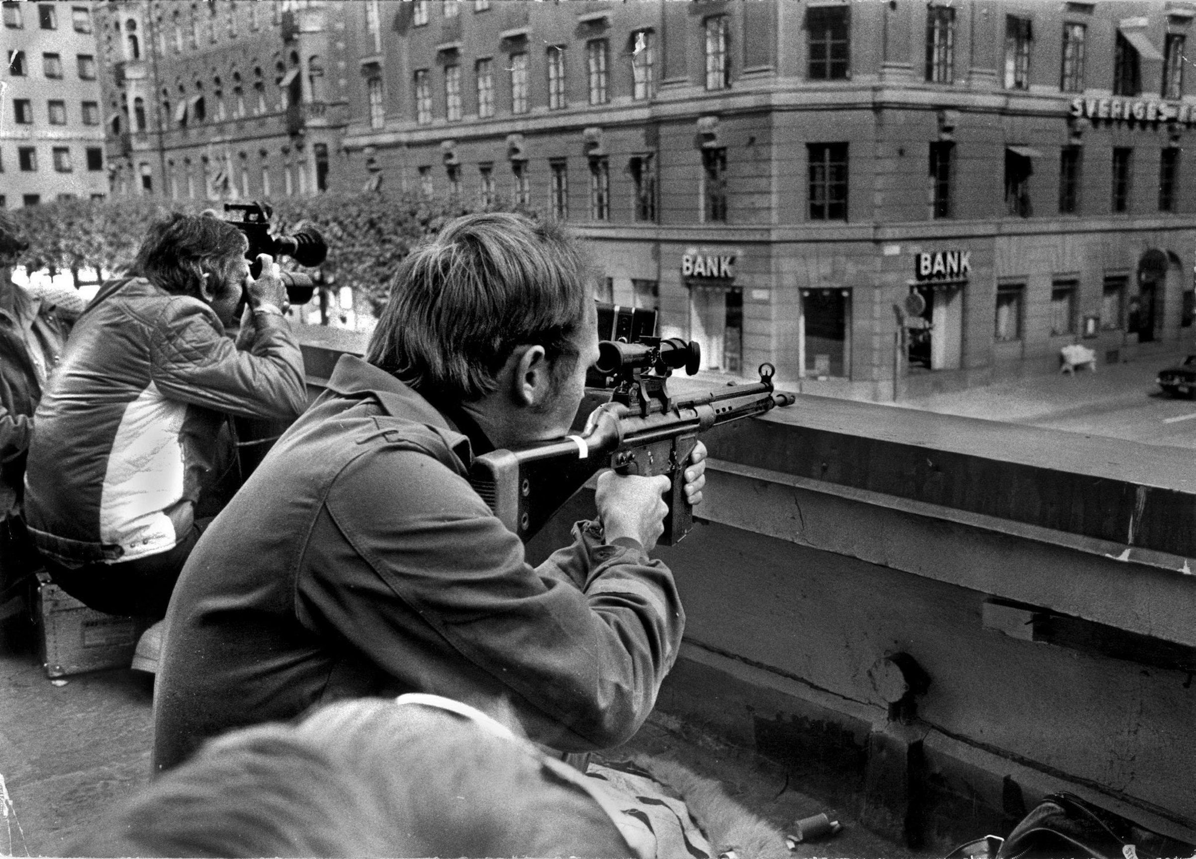 Press photographers and police snipers lie side by side on a roof opposite the Kreditbanken bank on Norrmalmstorg square in Stockholm on Aug. 24, 1973. A misfired robbery turned into a six-day standoff that gave birth to the phrase  Stockholm syndrome.