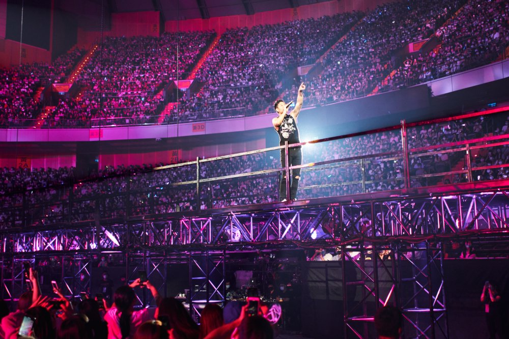 Chou performs on an extended platform near the back of the concert hall
