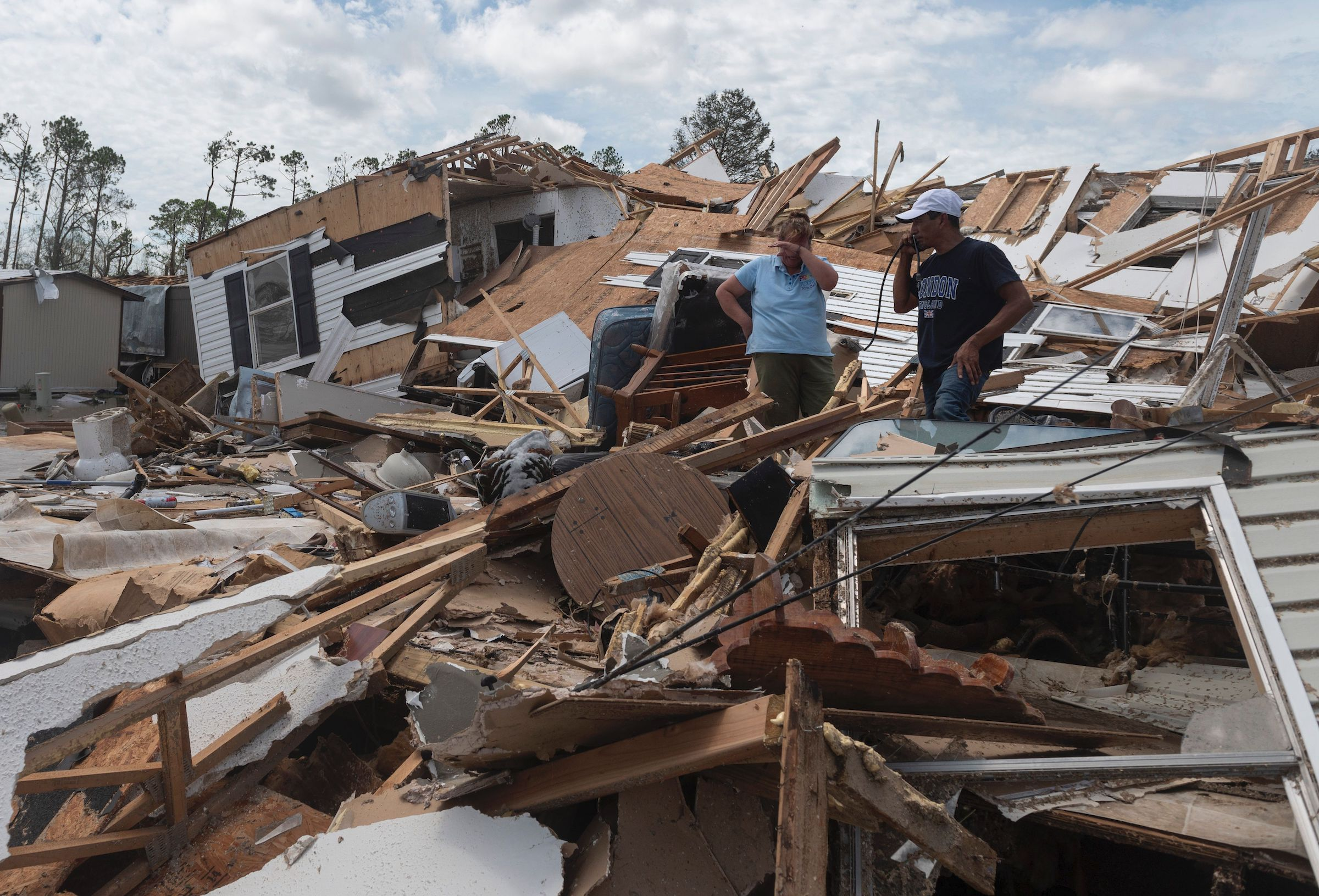 A couple react as they go through their destroyed mobile home following the passing of hurricane Laura in Lake Charles, La., on Aug. 27, 2020.