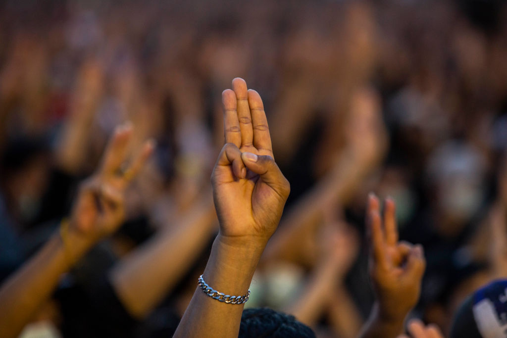 Protesters give a three-finger salute at a rally at the Democracy Monument in Bangkok, Thailand on Aug. 16, 2020.