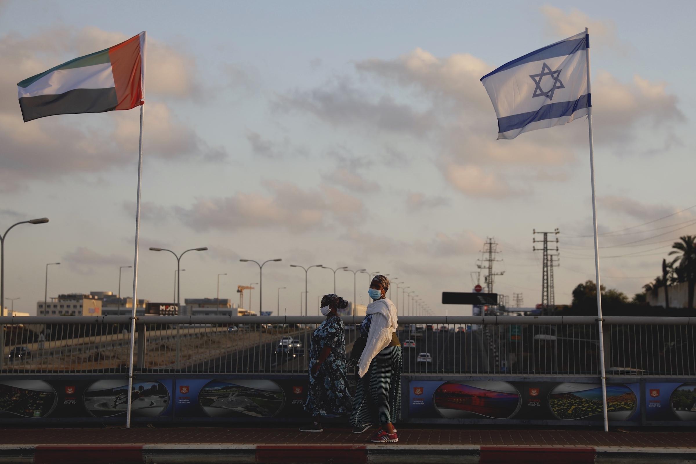 Women wear fave masks against the Coronavirus walk by United Arab Emirats and Israeli flags at the Peace Bridge in Netanya, Israel, Aug. 16, 2020.