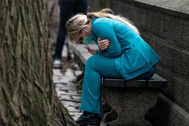 A healthcare worker sits on a bench near Central Park in New York City, on Mar. 30, 2020.