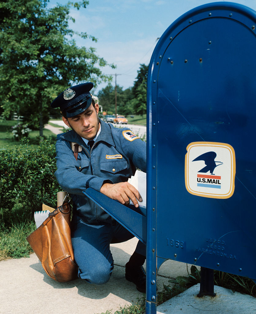 A 1970s mailman taking mail out of mail drop box