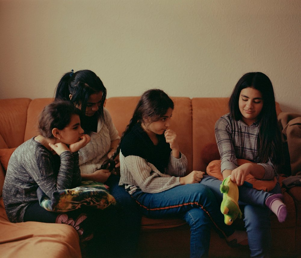 Hanan braiding her 11-year-old daughter Hanadi's hair while Berivan, 10 (L) and Haneya, 13 (R) watch.