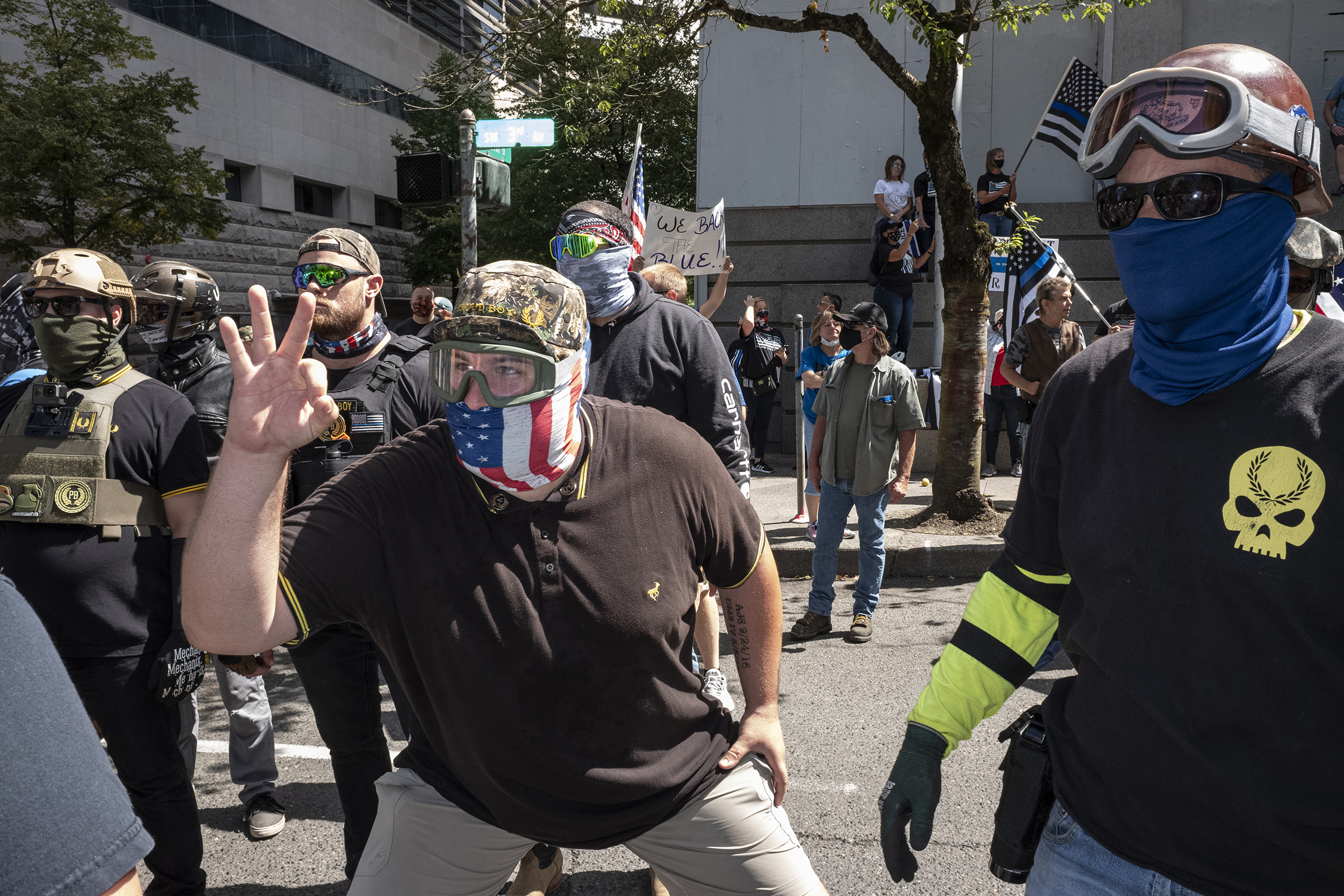 "An associate of the Proud Boys, a far-right group with a history of engaging in violent street clashes, flashes the once innocuous ""OK"" hand sign—now co-opted by white supremacists—at counter demonstrators during a rally in Portland, Ore., Aug. 22, 2020."