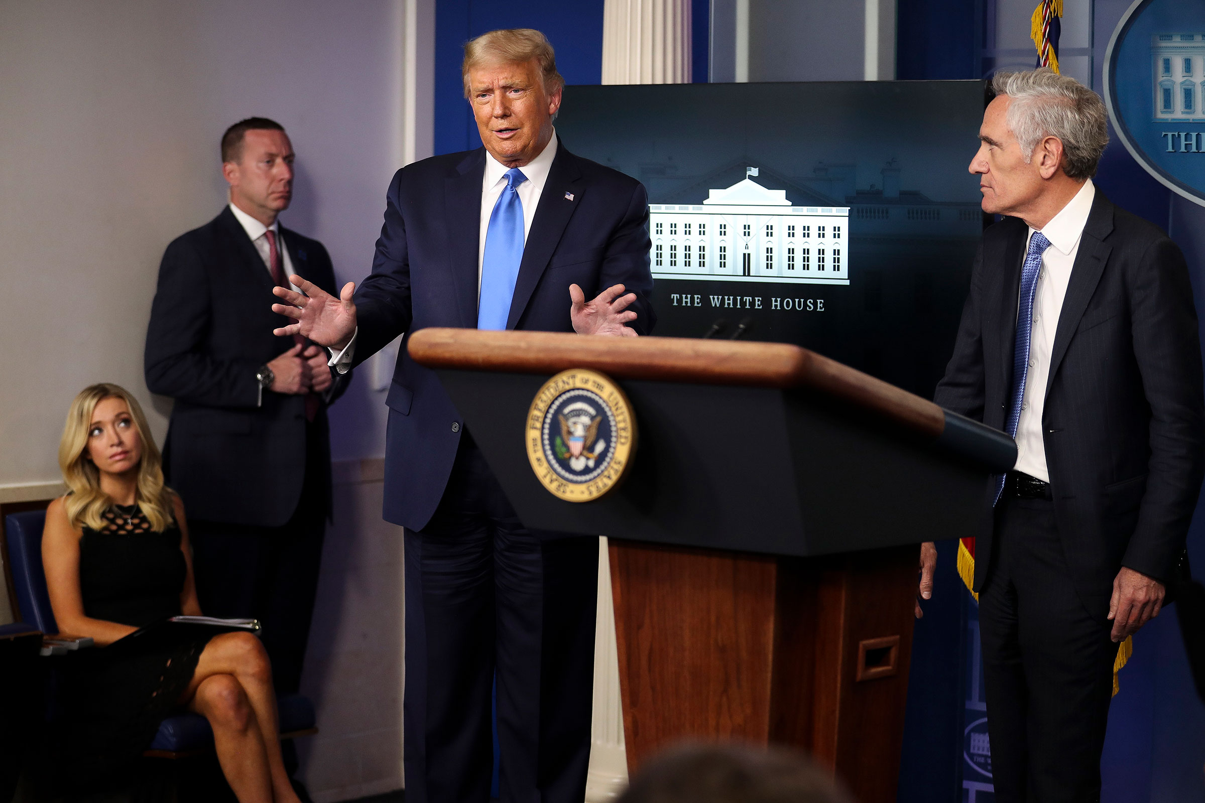 President Donald Trump speaks as Dr. Scott Atlas, a White House adviser on the coronavirus, right, and White House Press Secretary Kayleigh McEnany, far left, listen during a press briefing at the White House in Washington, on Wednesday, Sept. 23, 2020. (Oliver Contreras/The New York Times)