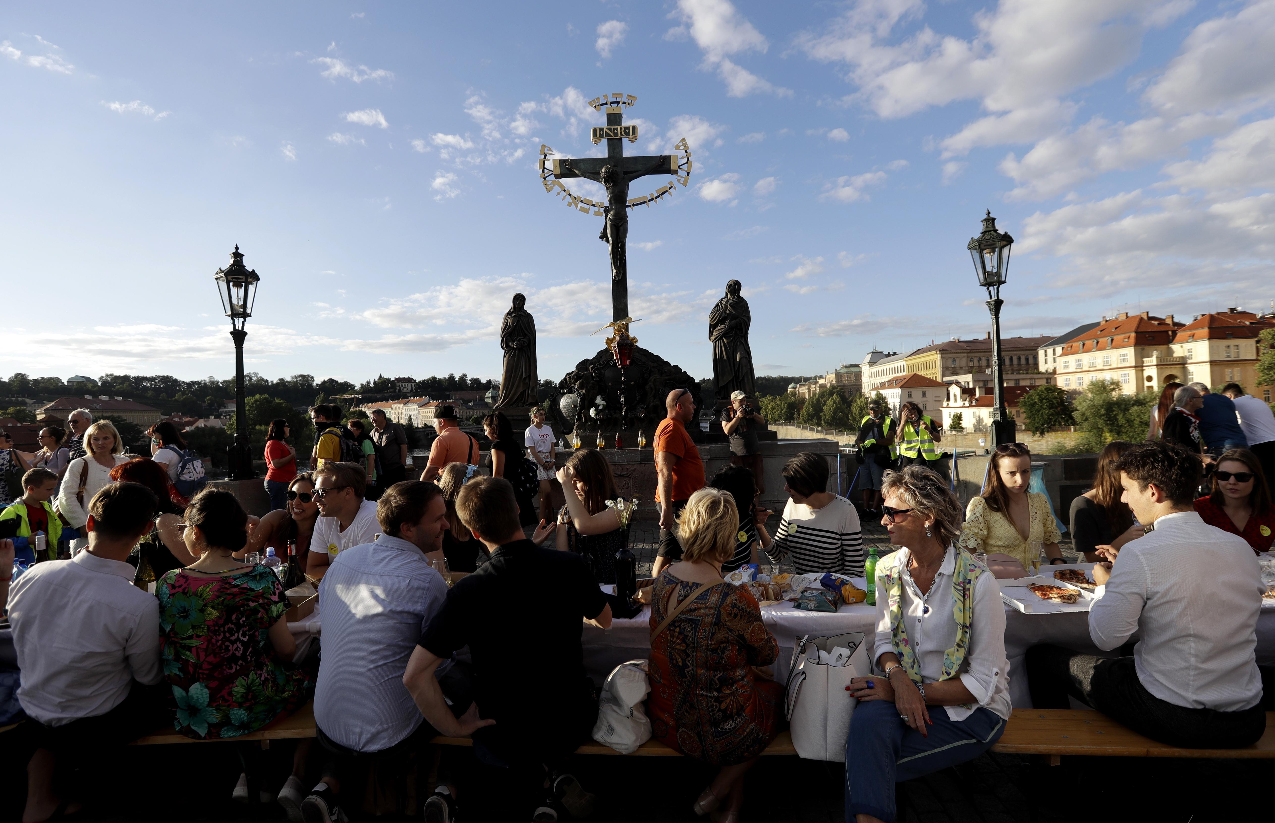 Os residentes sentam-se para jantar em uma mesa de 500 metros de comprimento colocada na ponte medieval Charles Bridge, depois que as restrições foram atenuadas após a pandemia de coronavírus em Praga, República Tcheca, terça-feira, 30 de junho de 2020.