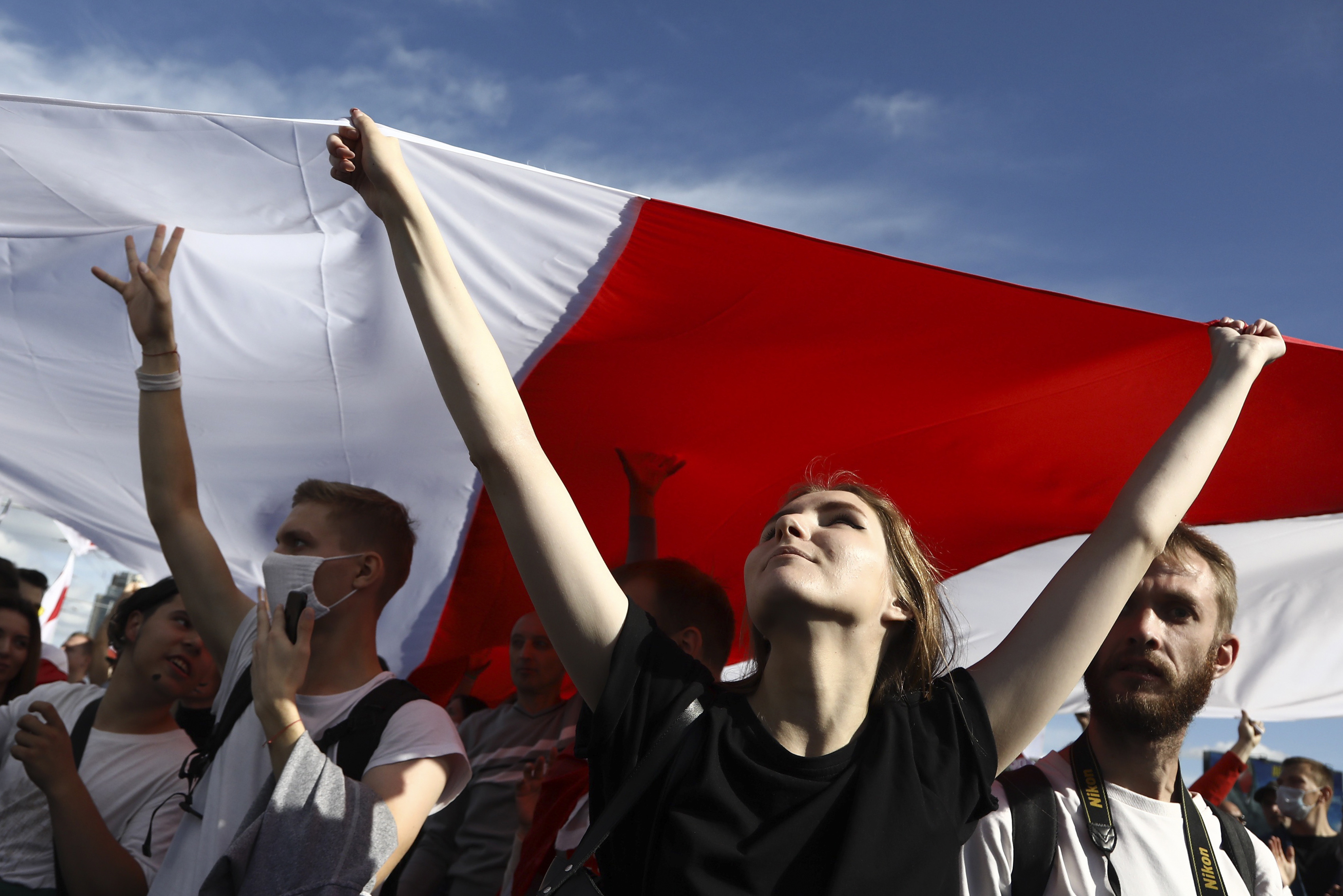 Protesters carry a giant old Belarusian national flag during a Belarusian opposition supporters' rally protesting the official presidential election results in Minsk, Belarus, Sunday, Sept. 13, 2020.