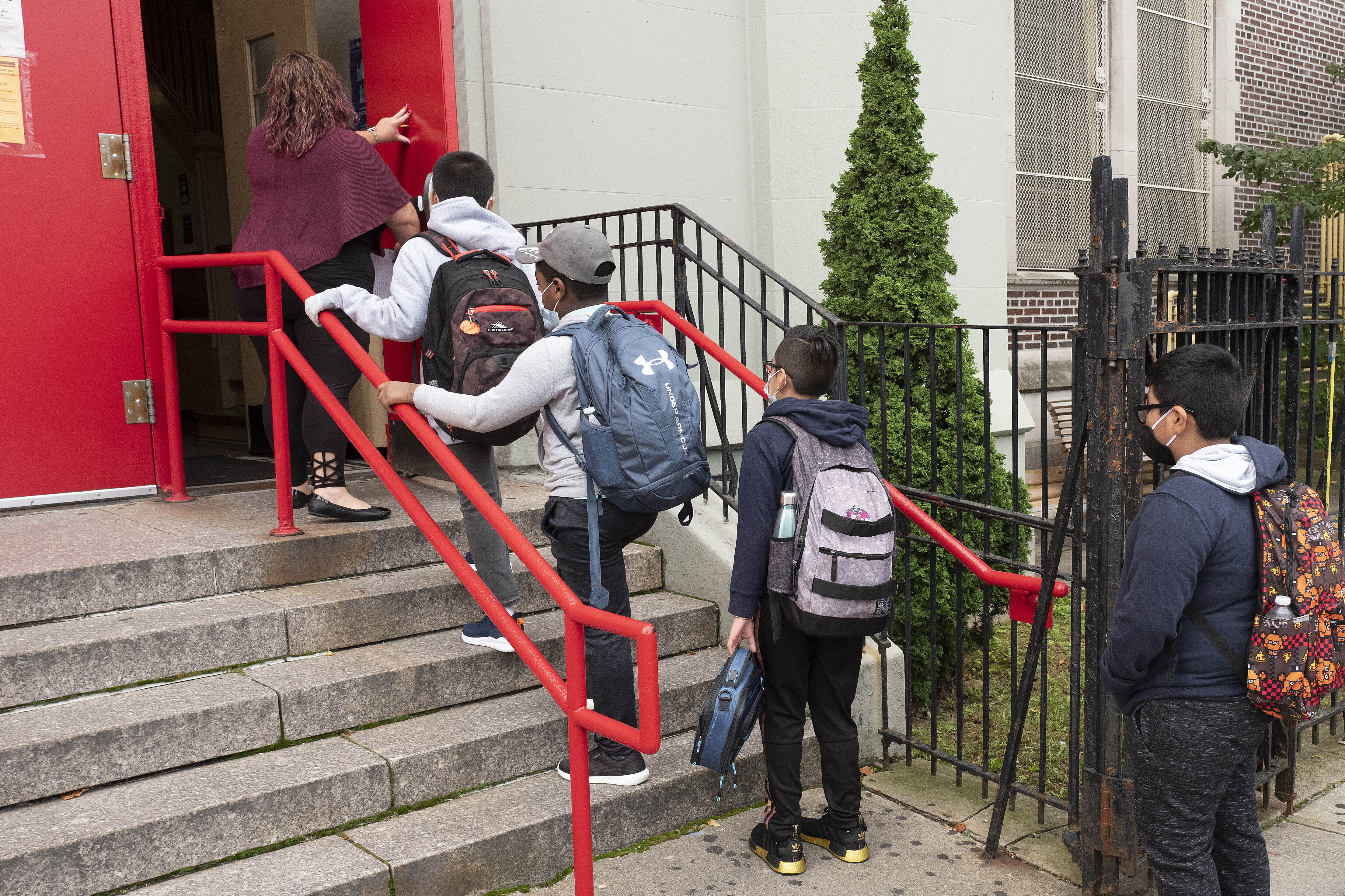 A teacher leads her students into an elementary school in the Brooklyn borough of New York on Tuesday, Sept. 29, 2020