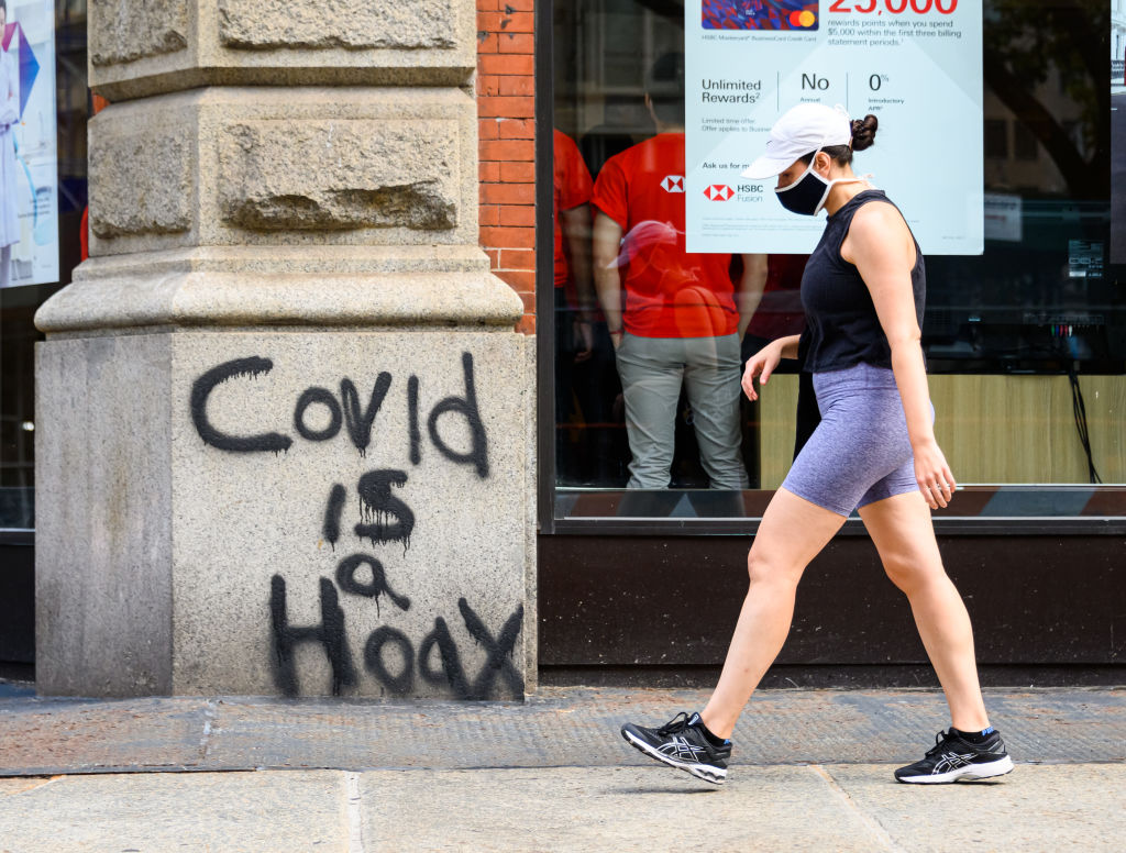 A person wears a protective face mask next to a graffiti that reads,  COVID is a hoax  in TriBeCa as the city continues Phase 4 of re-opening following restrictions imposed to slow the spread of coronavirus on Sept. 11 in New York City.