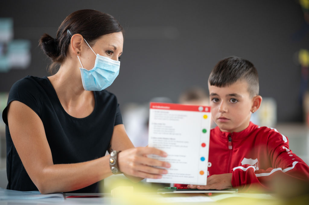 Teacher Judith Ziegler wears a mask while she is tutoring a pupil at a primary school on August 31, 2020 in Baden-Wuerttemberg, Hemmingenin in Germany.