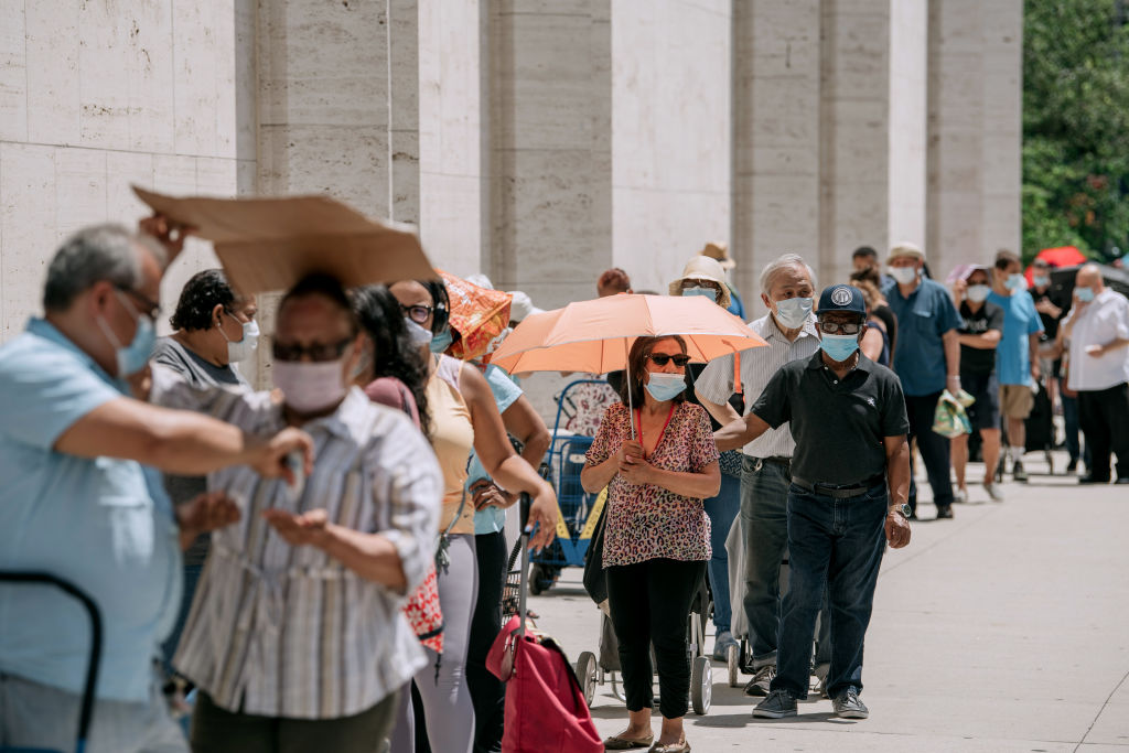 New Yorkers in need wait in a long line to receive free produce, dry goods, and meat at a Food Bank For New York City distribution event at Lincoln Center in New York City on July 29, 2020.