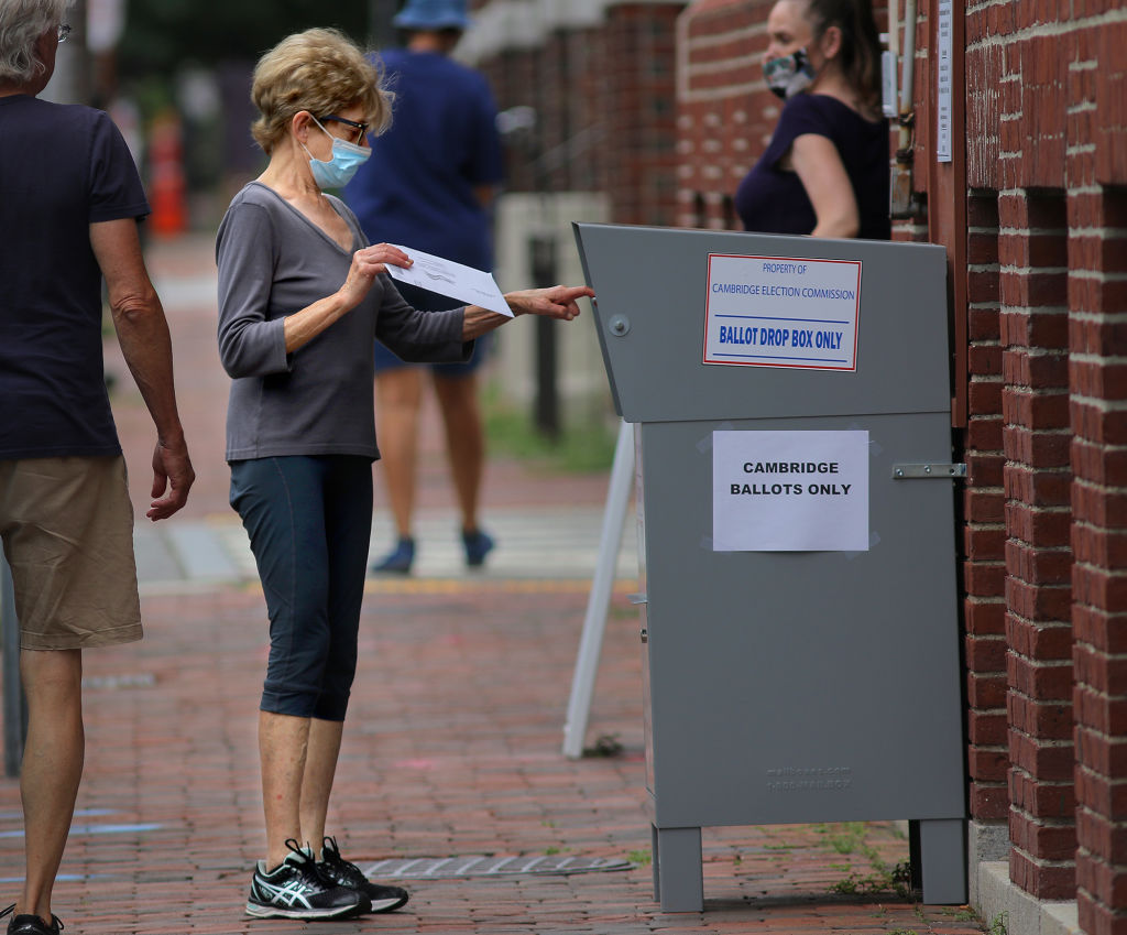 A voter drops off a mail-in ballot in a collection box in Cambridge, Mass. on Aug. 25.
