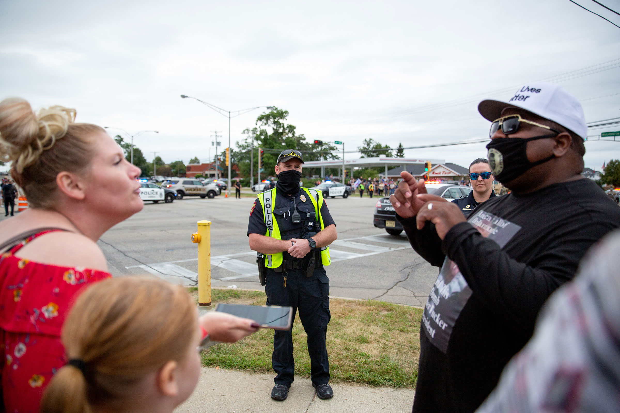 Police watch protestors during President Trump's meeting at Bradford High School in Kenosha, Wis., on Sept. 1, 2020.