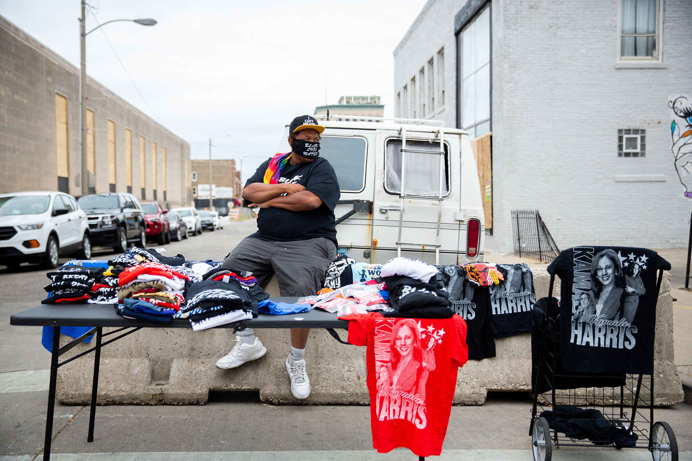 A street vendor selling T-shirts observes a crowd of protesters marching near the county courthouse in Kenosha, Wis., on Sept. 1, 2020.