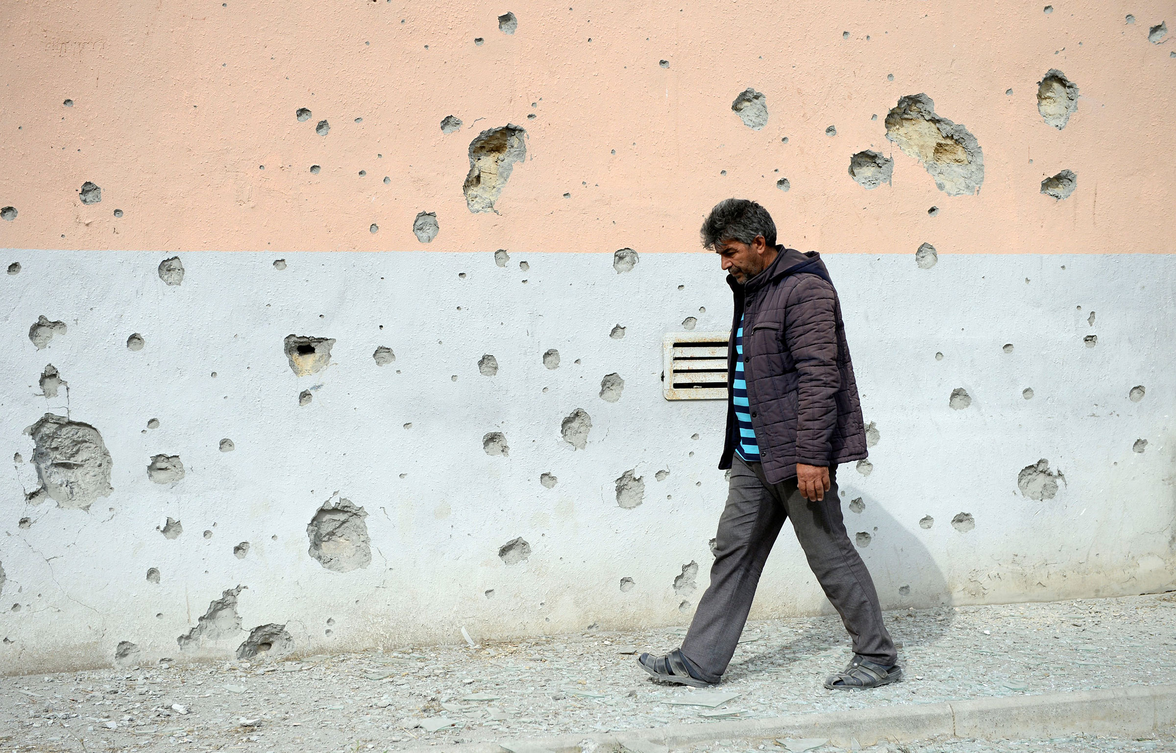 A man walks by a house that was damaged during clashes in the Tartar district bordering the Nagorno-Karabakh region, on Sept. 29, 2020.