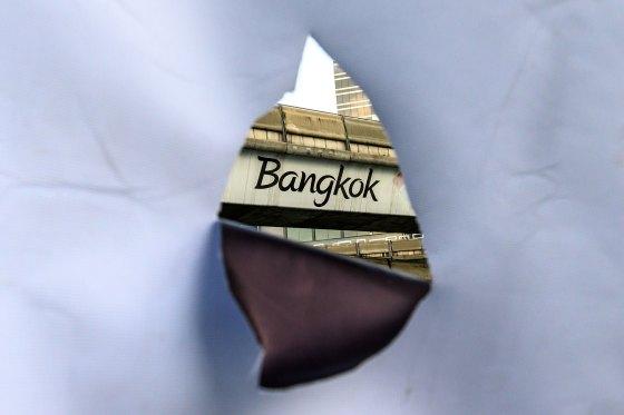 A Bangkok inscription on a sky train bridge is seen through the hole of a banner