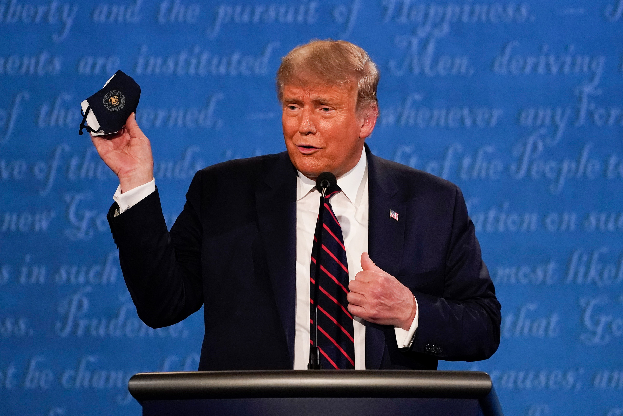 President Donald Trump holds out his face mask during the first presidential debate at Case Western University and Cleveland Clinic, in Cleveland on Sept. 29, 2020.