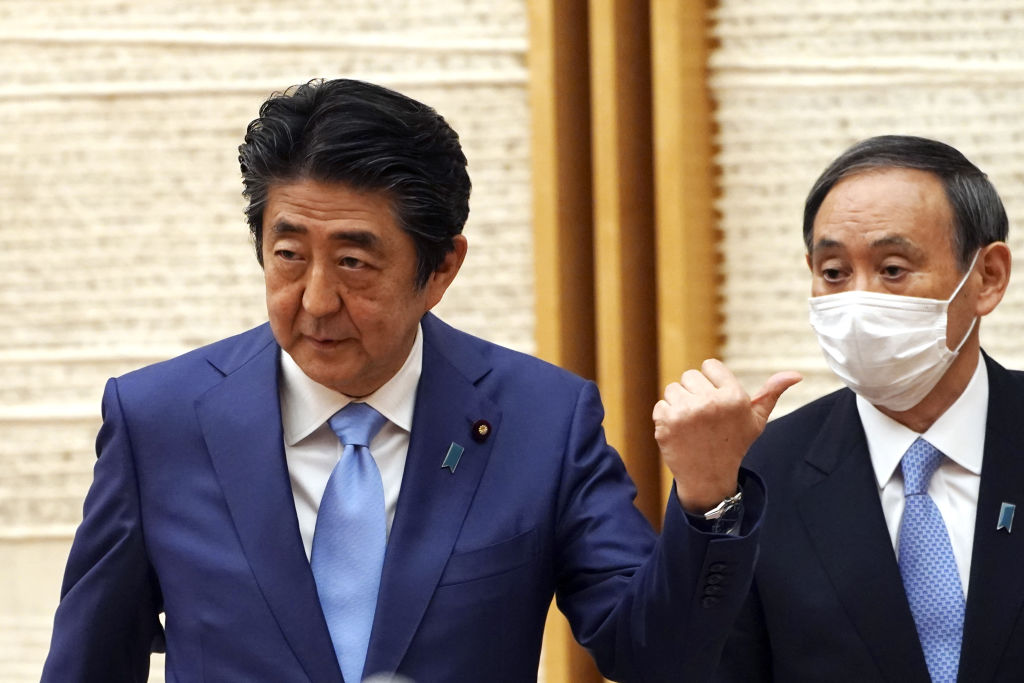 Japanese Prime Minister Shinzo Abe, left, gestures toward Chief Cabinet Secretary Yoshihide Suga during a news conference in Tokyo, Japan, on Monday, May 4, 2020. Suga is expected to succeed Abe, who is stepping down due to health problems.