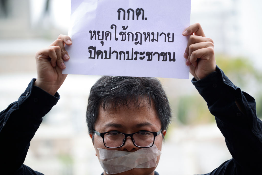 Human rights lawyer Arnon Nampa holds a poster during election protests in Bangkok, Thailand on April 7, 2019.