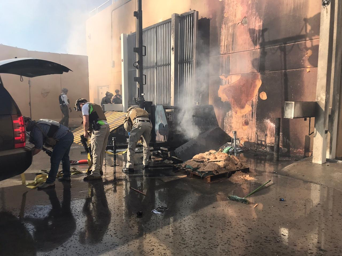 DSS Special Agent Evan Tsurumi, front-center, helps to remove a burning obstacle during an attack on the U.S. embassy in Baghdad. In the background, DSS Special Agent Mike Yohey and others examine ways to barricade an entrance at the embassy.