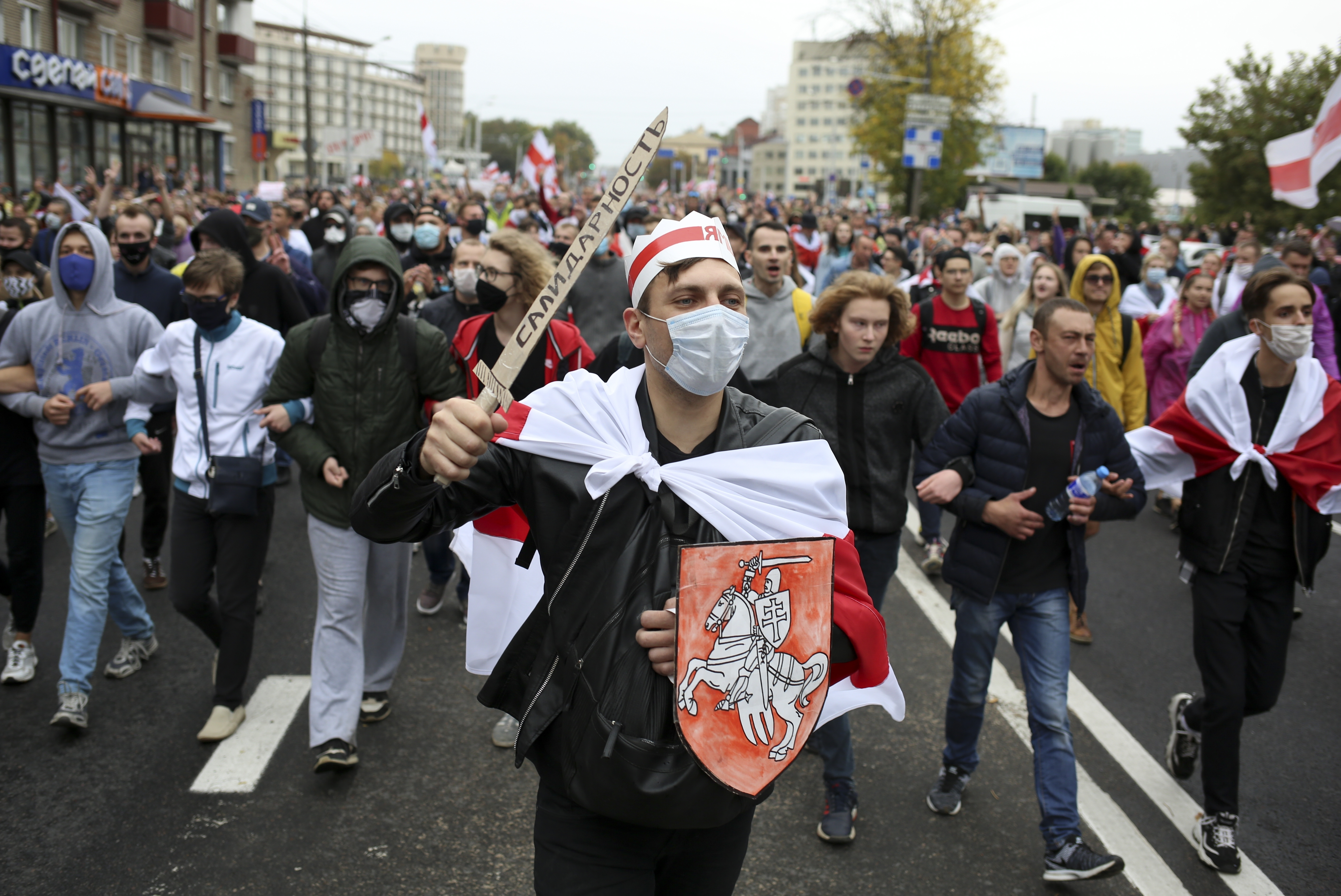 Demonstrators, one of them wearing an old Belarusian nation flag and holding a cardboard sword reading  solidarity  march during an opposition rally to protest the official presidential election results in Minsk, Belarus, Sept. 27, 2020.