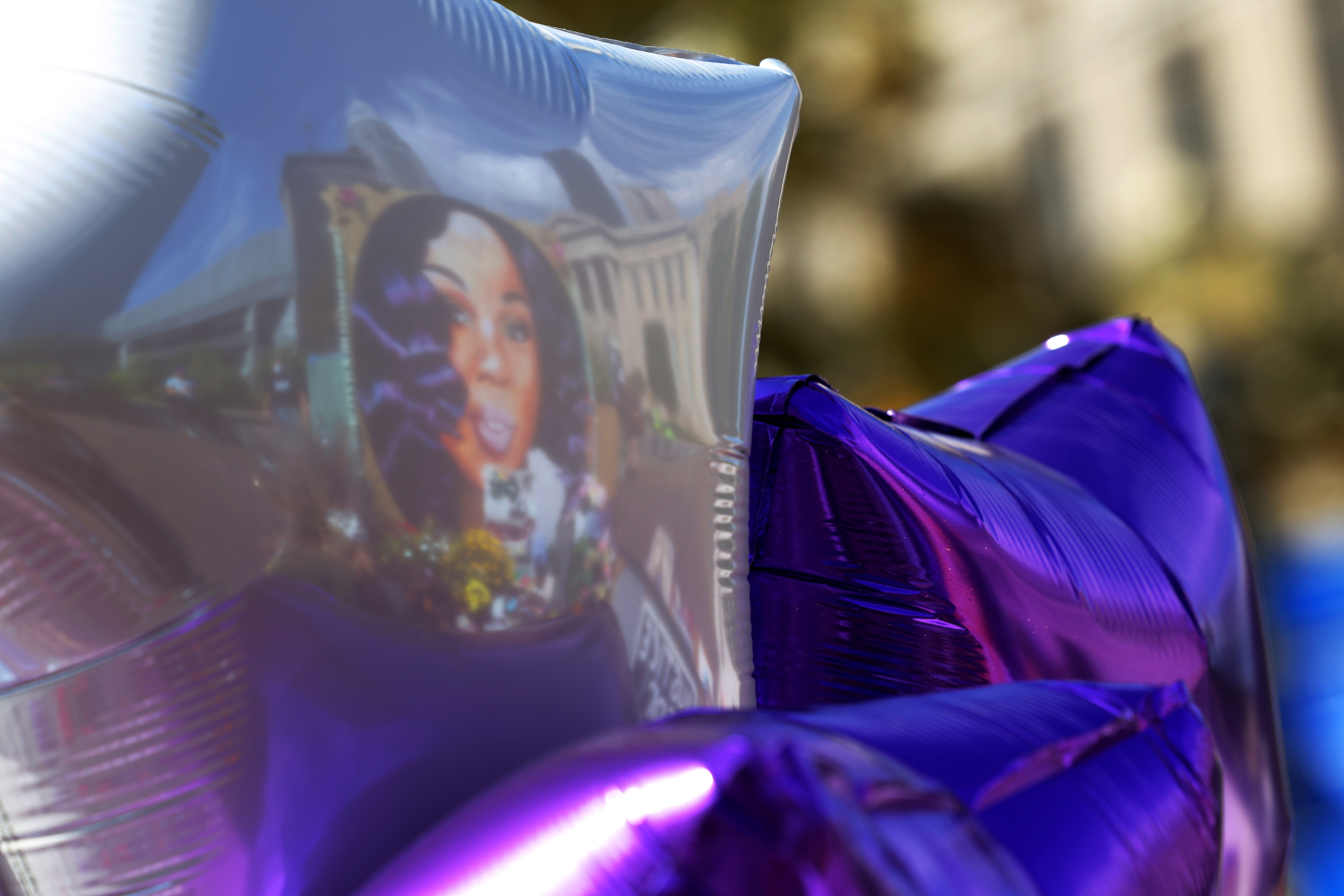 A mural of Breonna Taylor reflected on balloons left at her makeshift memorial in Jefferson Square Park on Sept. 24, 2020 in Louisville, Kentucky.